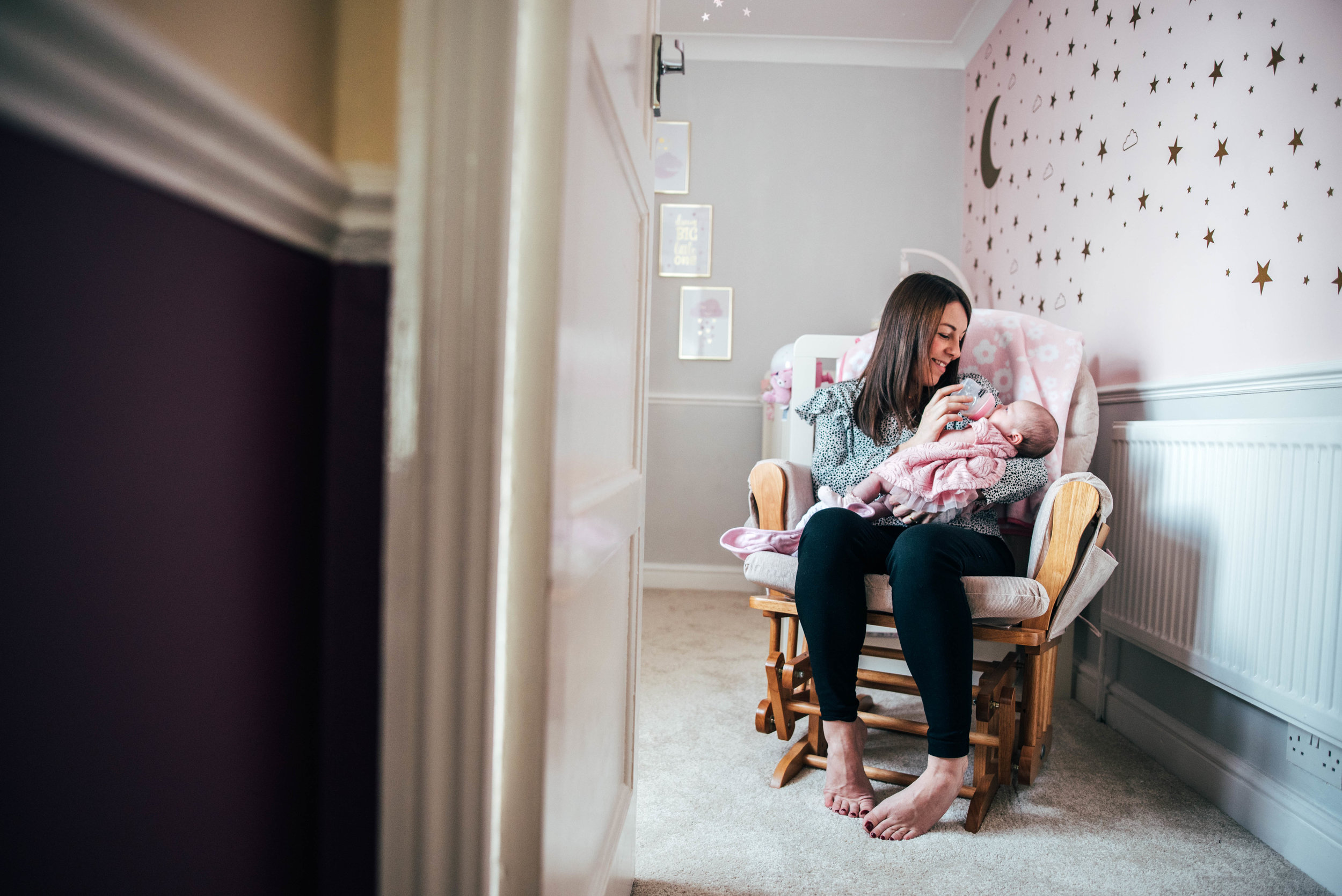 Mum feeds her new baby in nursery Essex Documentary Family Portrait Photographer