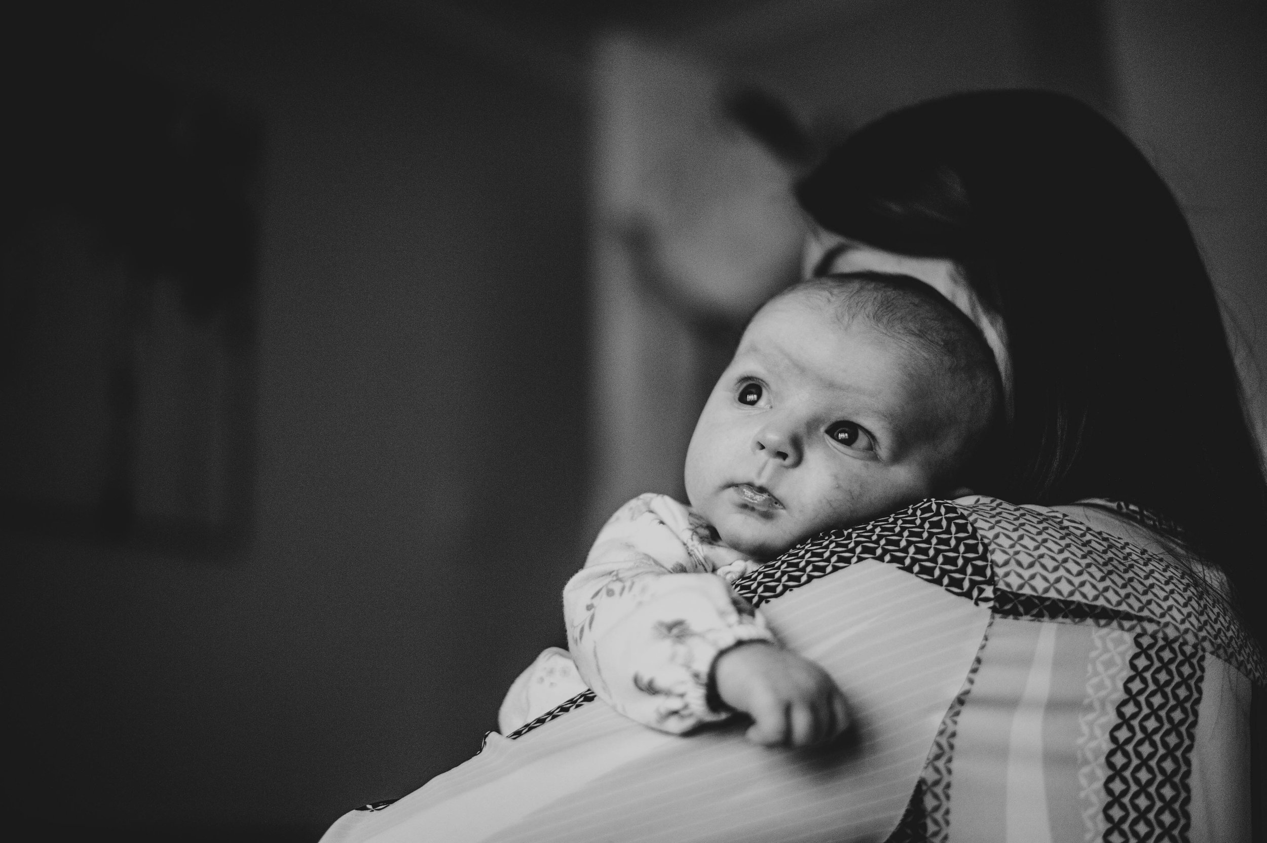 Baby girl rests on mums shoulder at home Essex Documentary Family Portrait Photographer