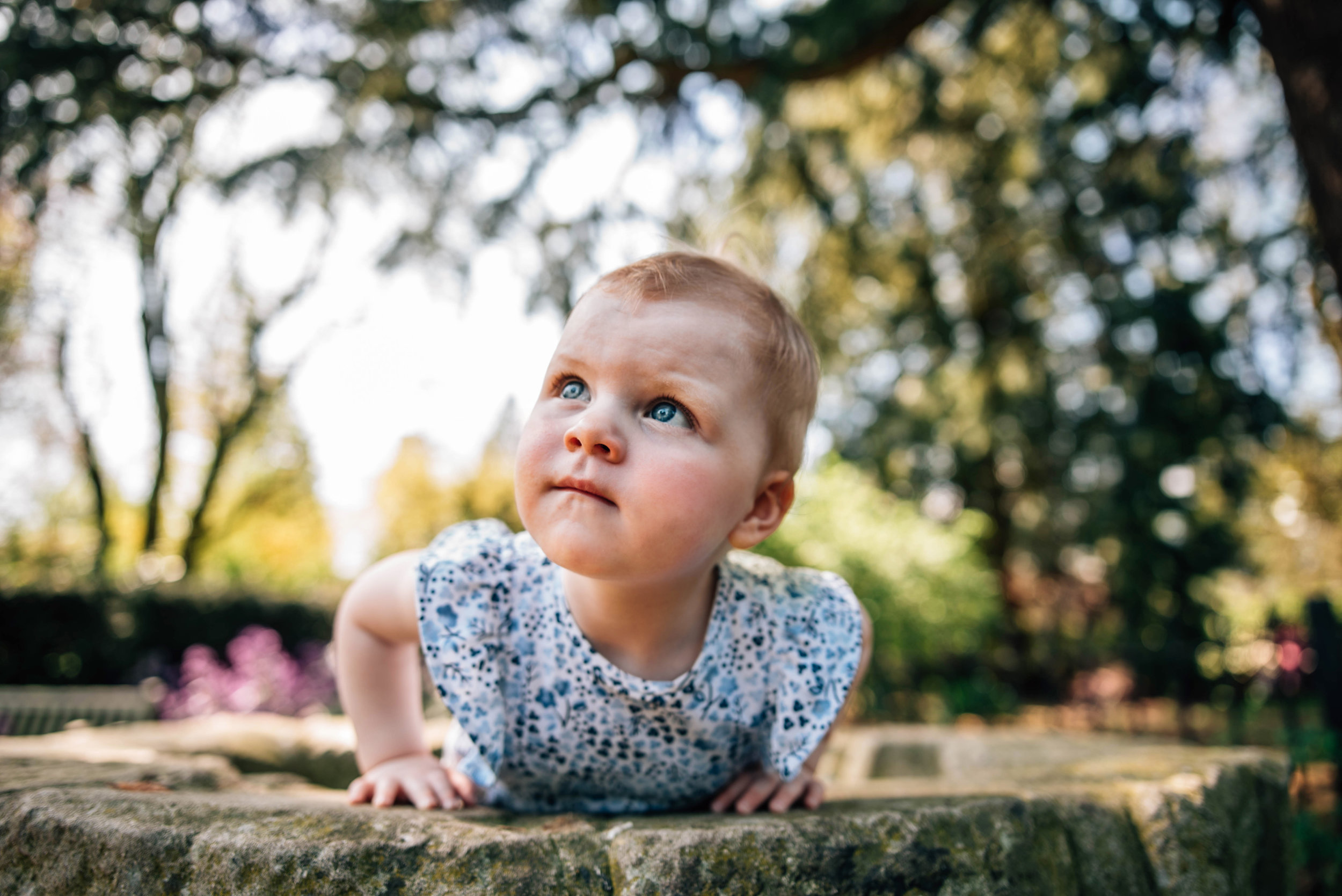 Toddler girl leans out of well in gardens Essex Documentary Family Portrait Photographer