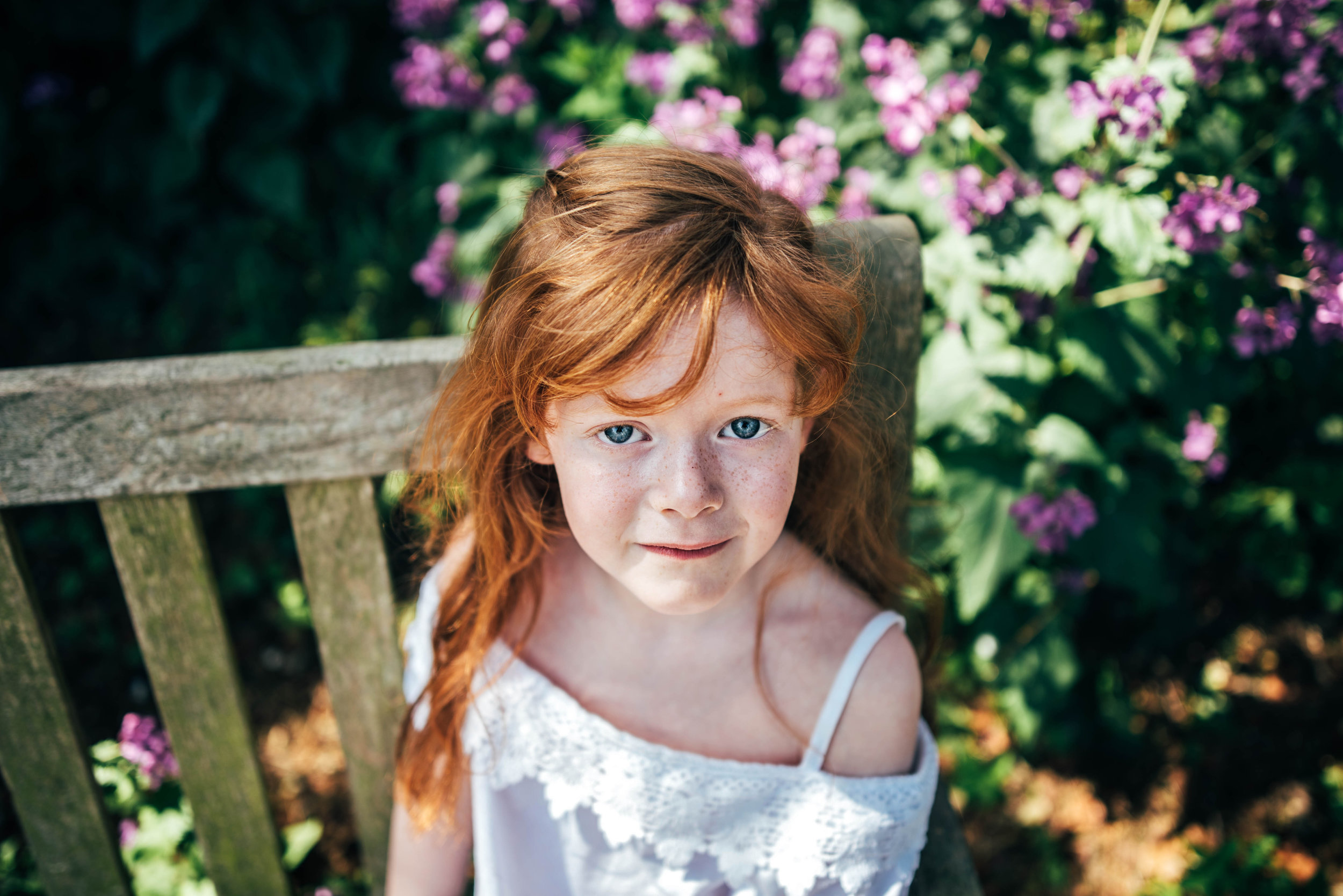Red haired girl looks up at camera from a bench Essex Documentary Family Portrait Photographer