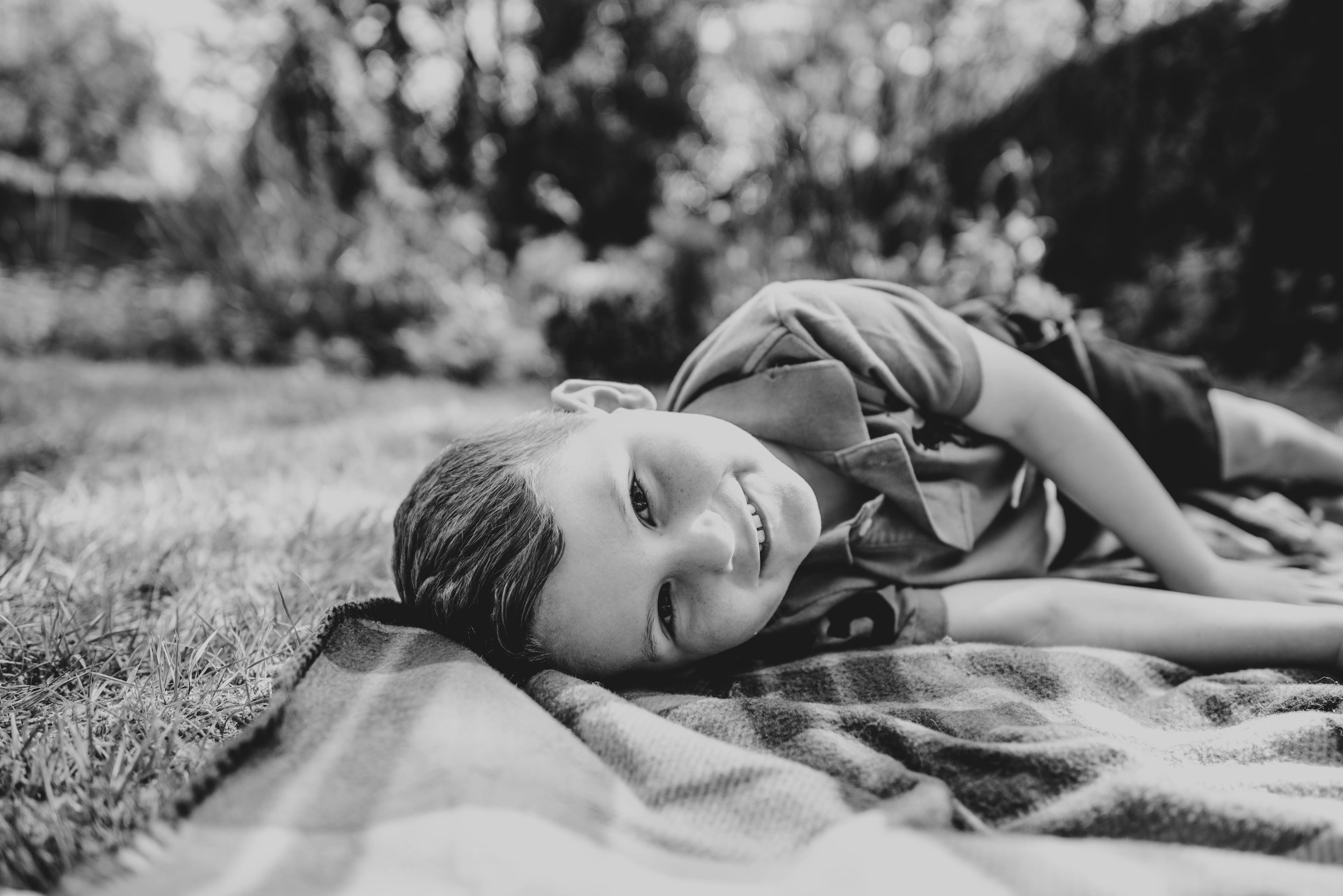 Little boy looks at camera while lying on a blanket Essex Documentary Family Portrait Photographer