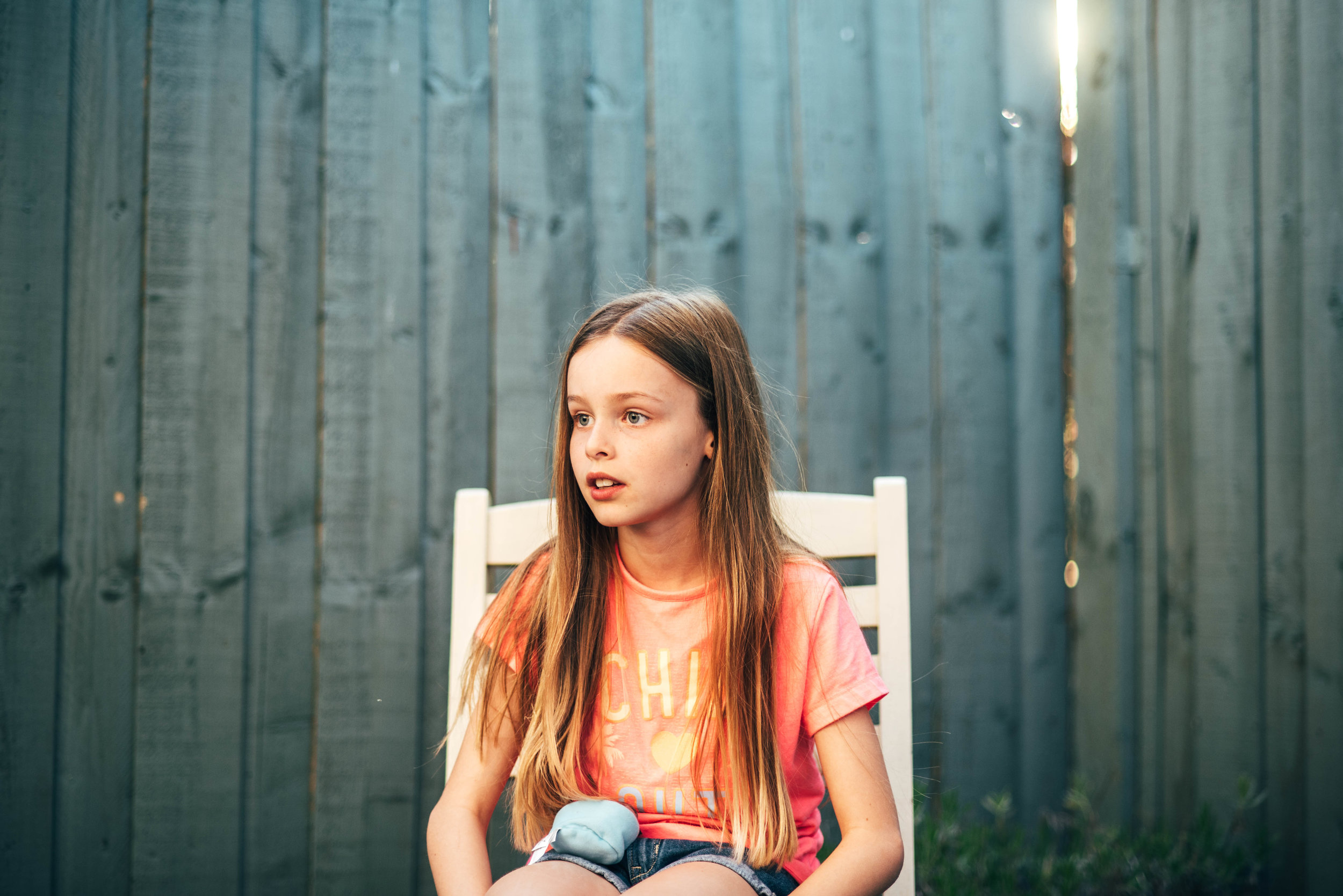 Girl sits on a garden chair Golden Hour Essex documentary Family Photographer