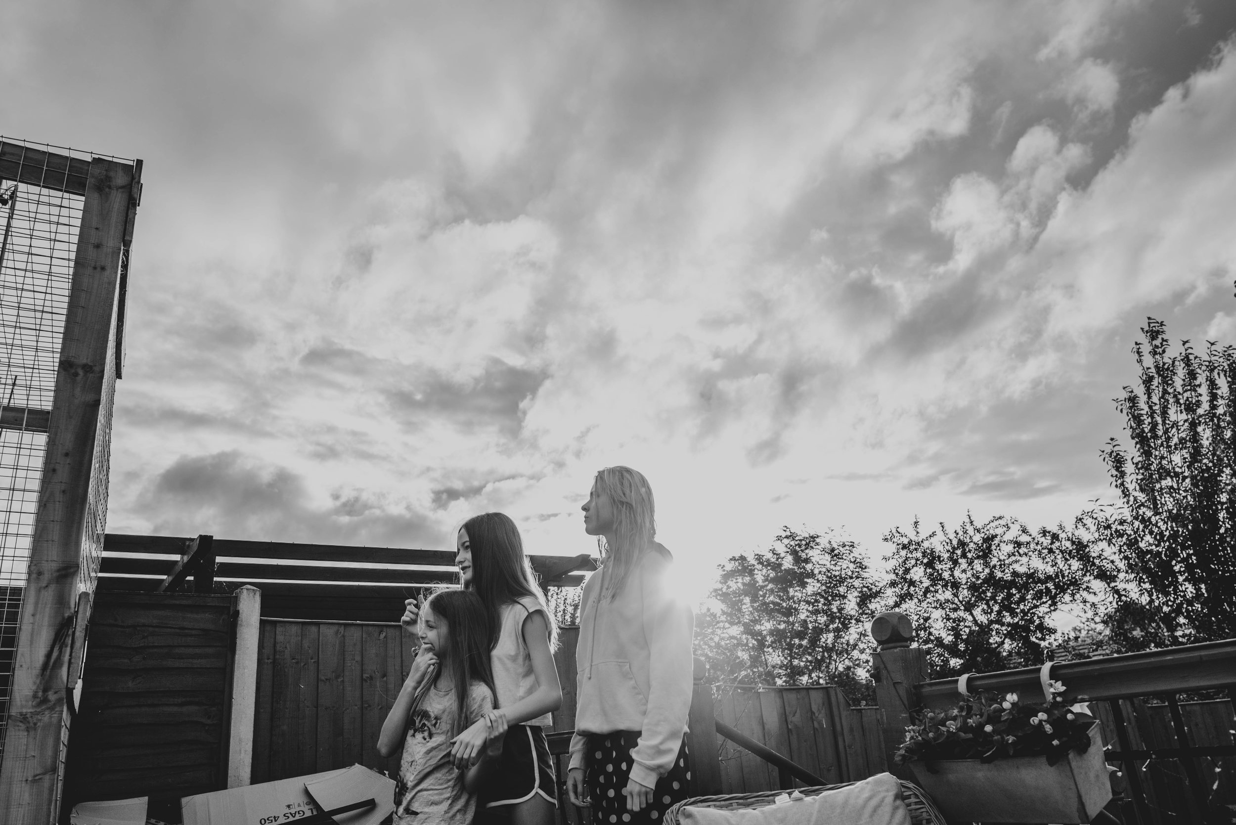 Three sisters dance in garden at sunset Essex Documentary Family Photographer