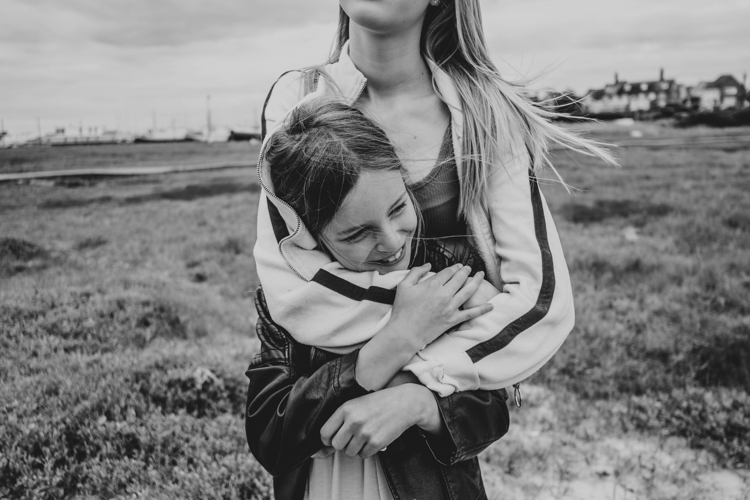 Two sisters hug on a beach Essex Documentary Family Photographer