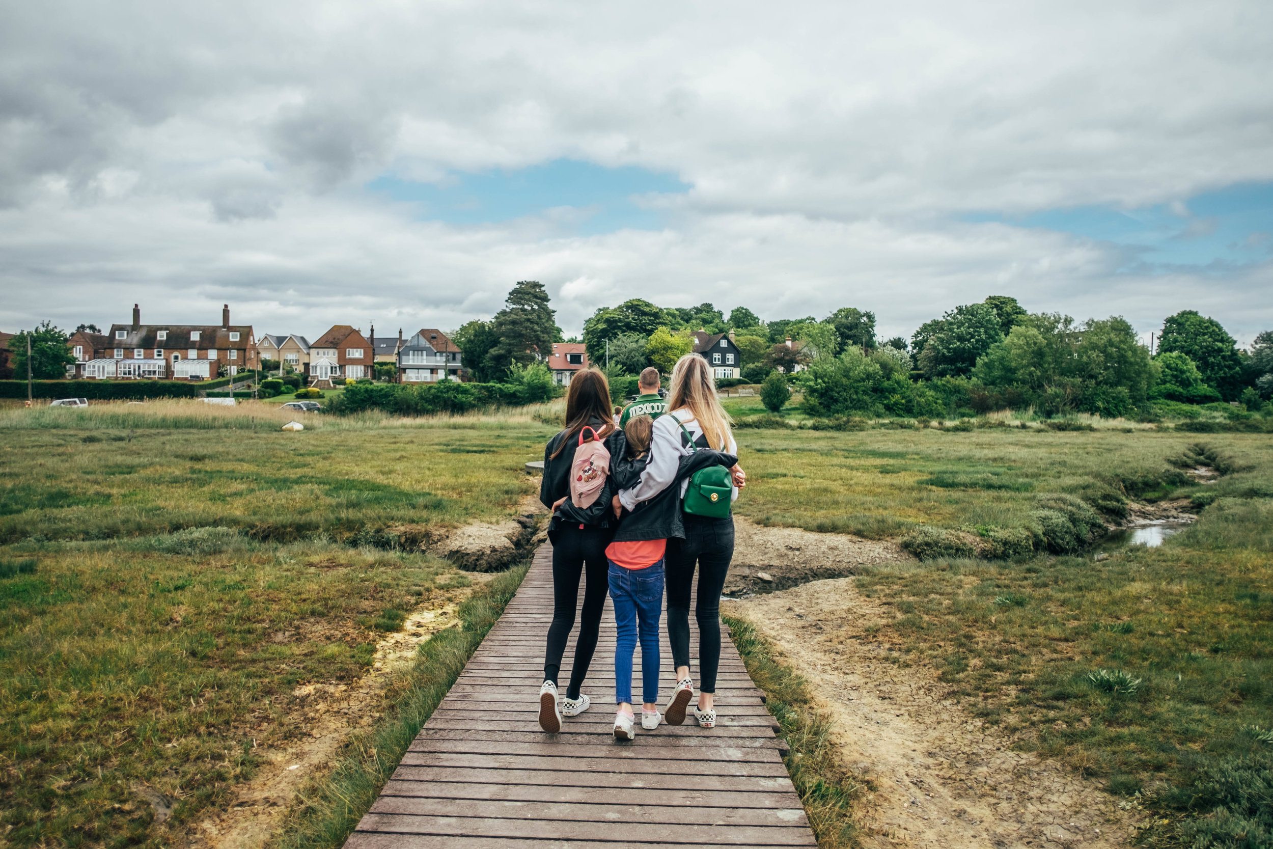 Three sisters on boardwalk at Mersea Essex Documentary Family Photographer