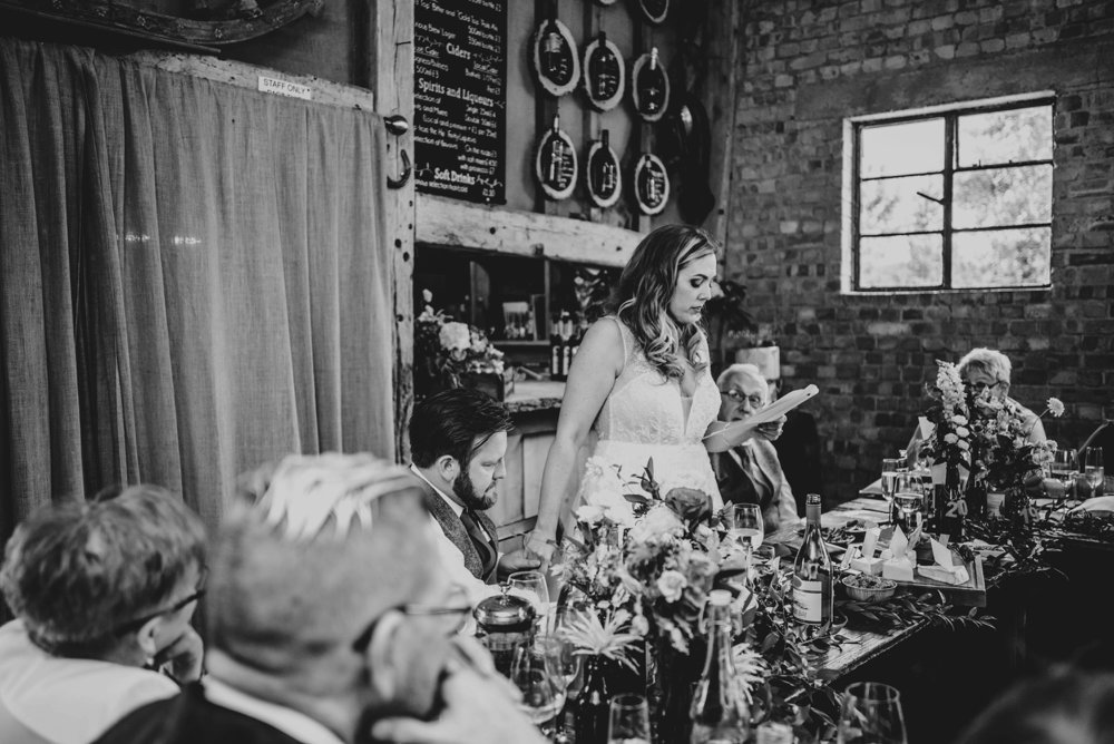 Lush, Vibrant Reds and Tweed for a Movie inspired Barn wedding at The House Meadow with Bridesmaids in Jumpsuits and a Festival Vibe. Essex Documentary Wedding Photographer