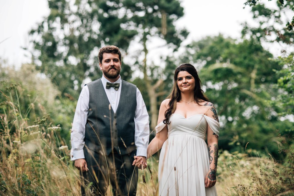 A Sage, Grey & White Festival Wedding with Brass detail at Lodge Farm, Lindsey. Tattooed Bride and Dog in a bow tie. Essex Documentary Wedding Photographer