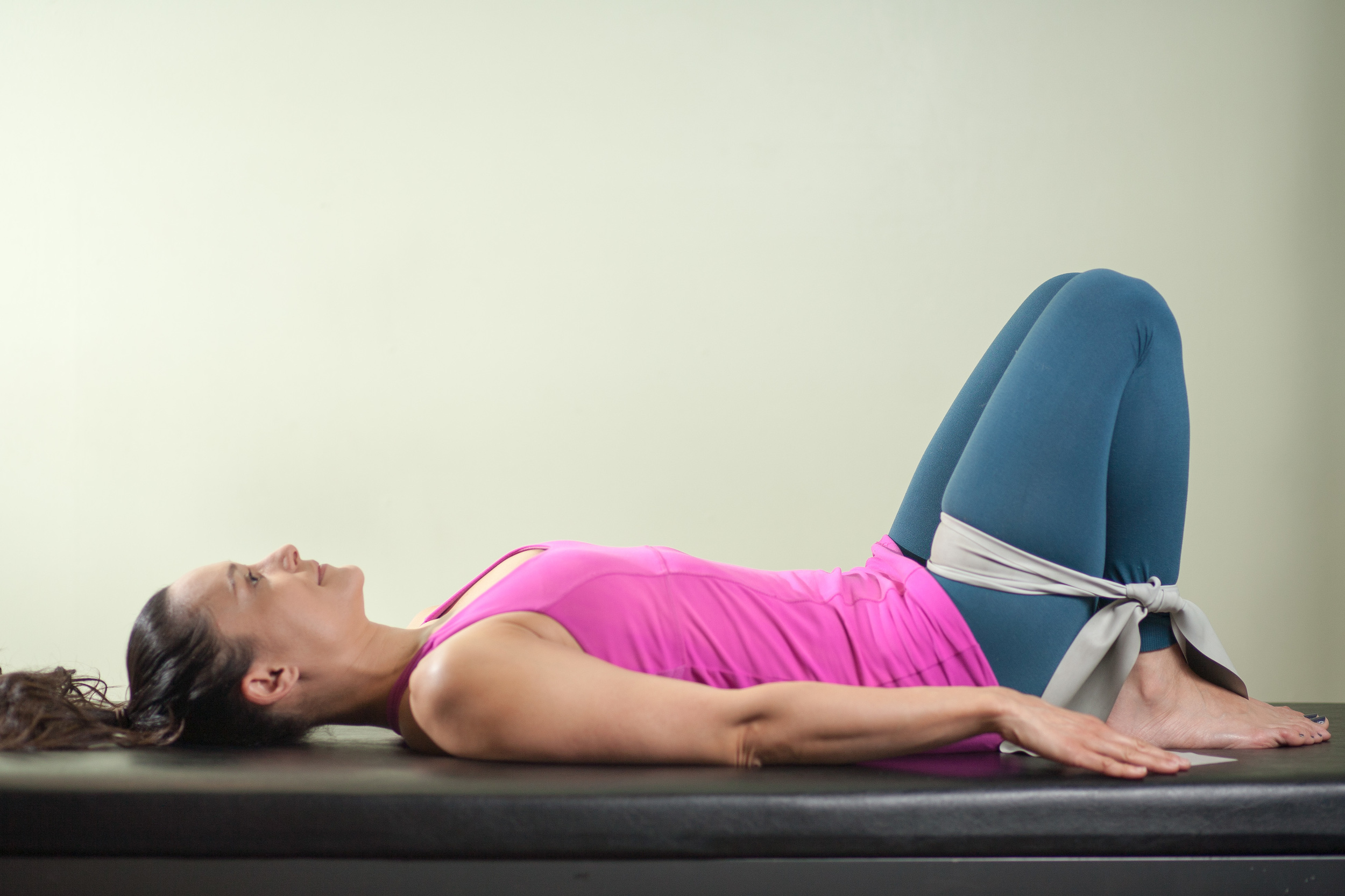 Woman using thera-band to exercise her Psoas msucle.
