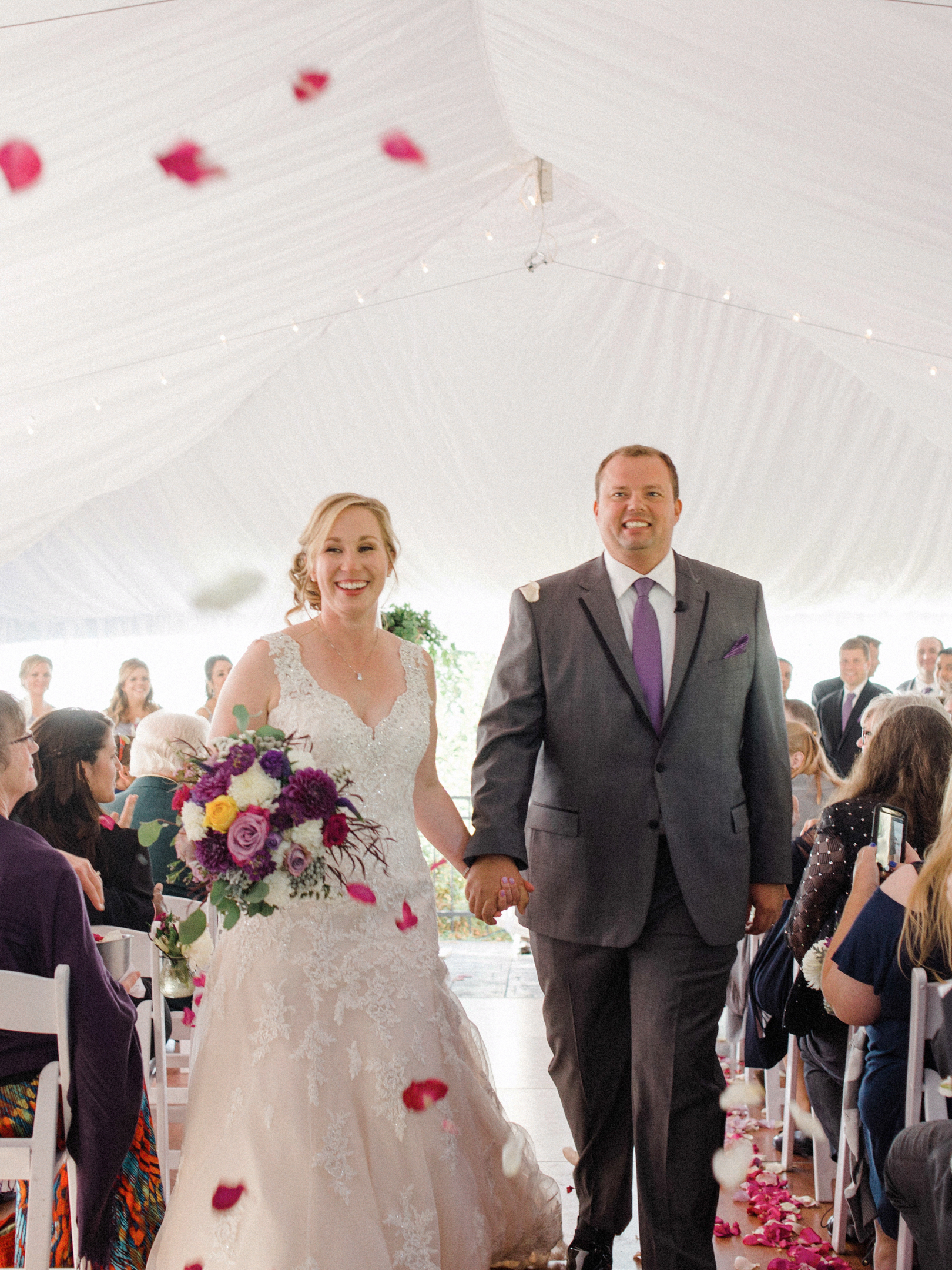 bride and groom recess down the aisle at door county tent wedding