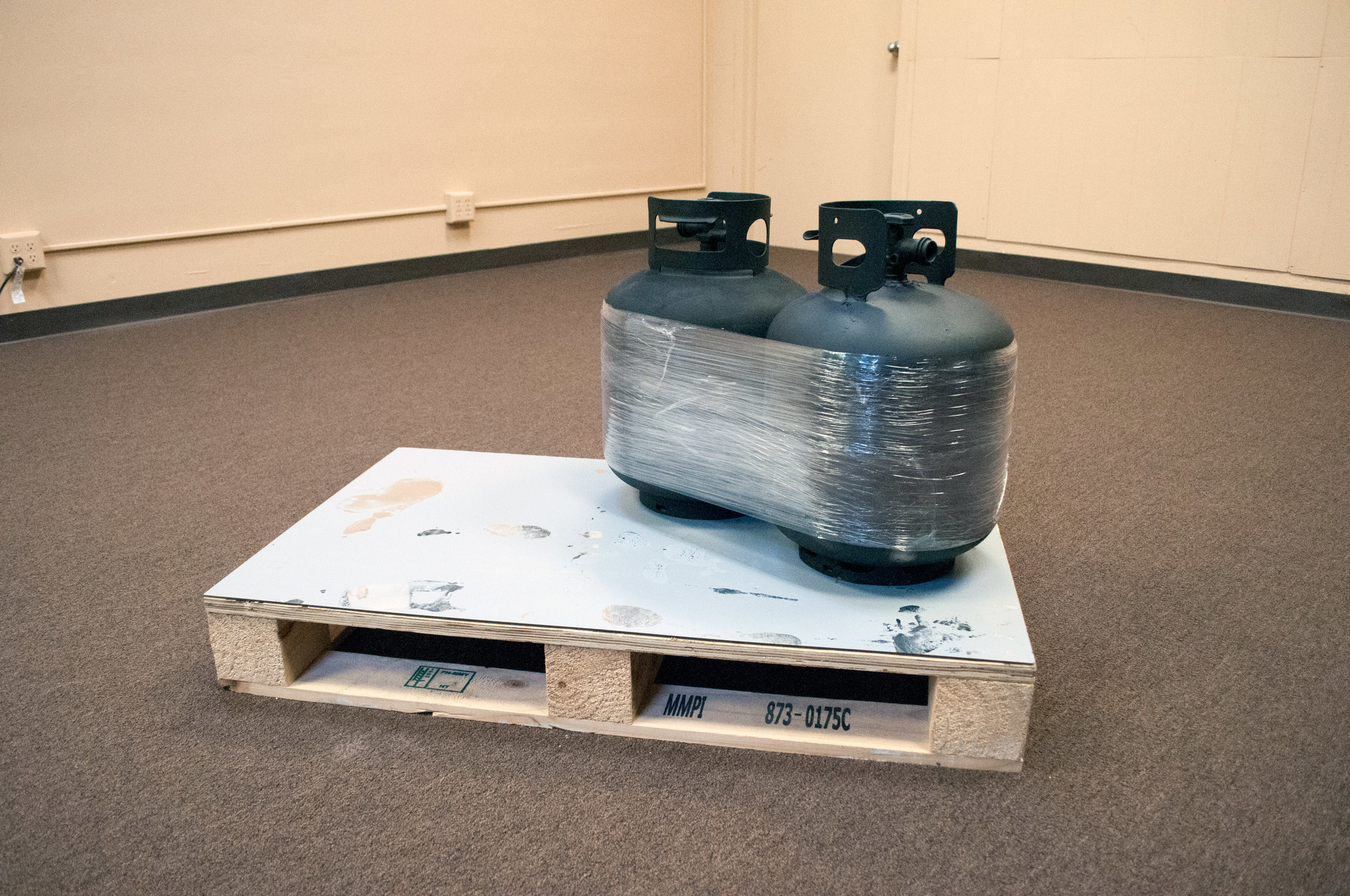 From the Beginning We Always Knew We Weren't Gonna Make It (After Brancusi's Kiss), 2016,  2 propane cylinder tanks, clear plastic stretch wrap, matte black spray paint, recycled wood pallet.