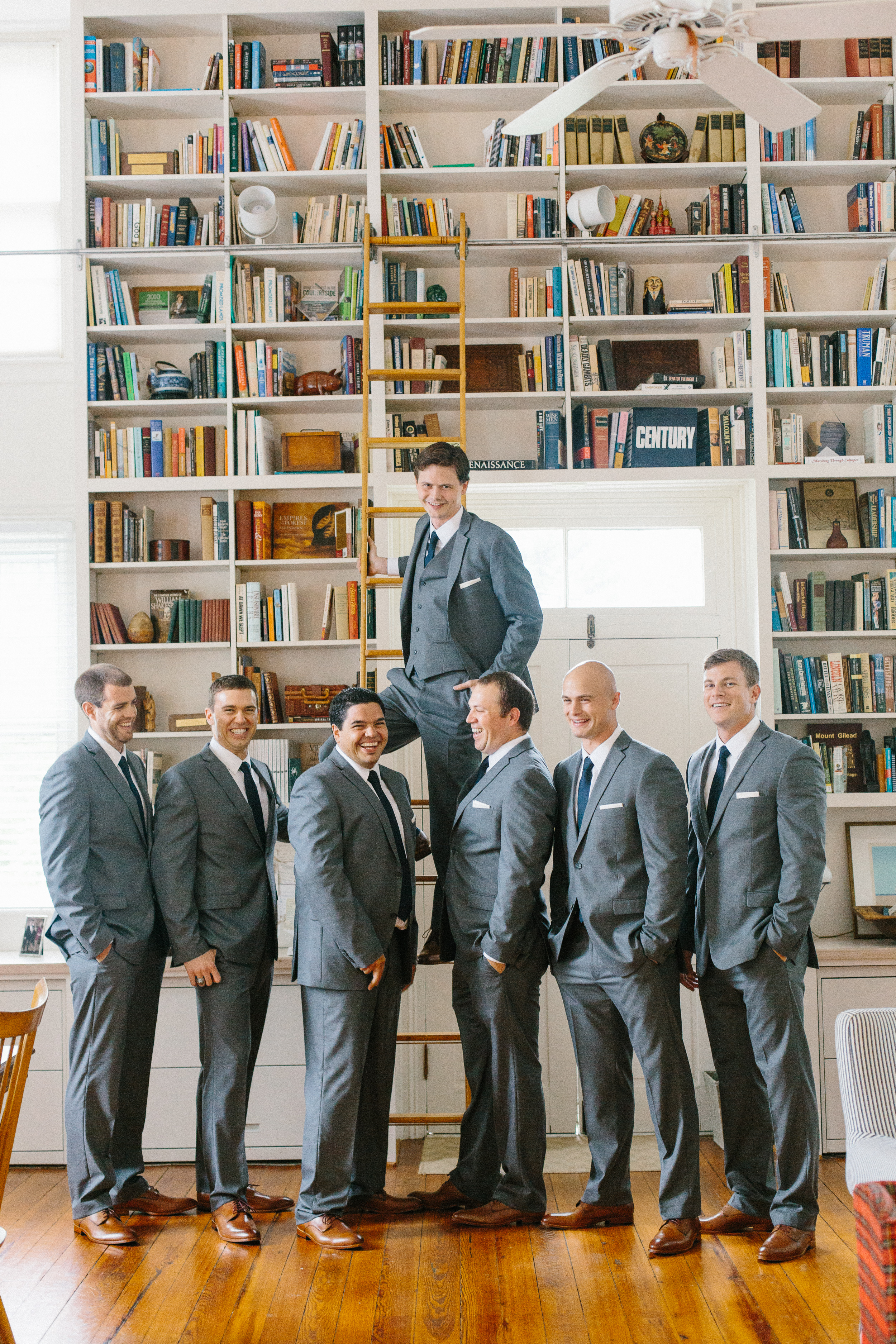 groomsmen-group-photo-wall-of-books