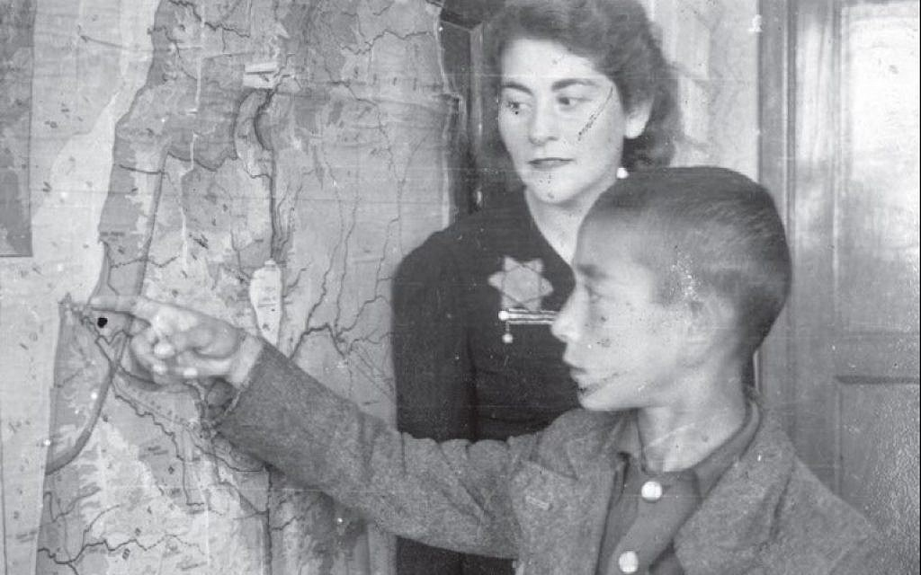 A teacher and a student near a map of the Land of Israel in the Łódź ghetto, Poland. (Yad Vashem Archives Collection)