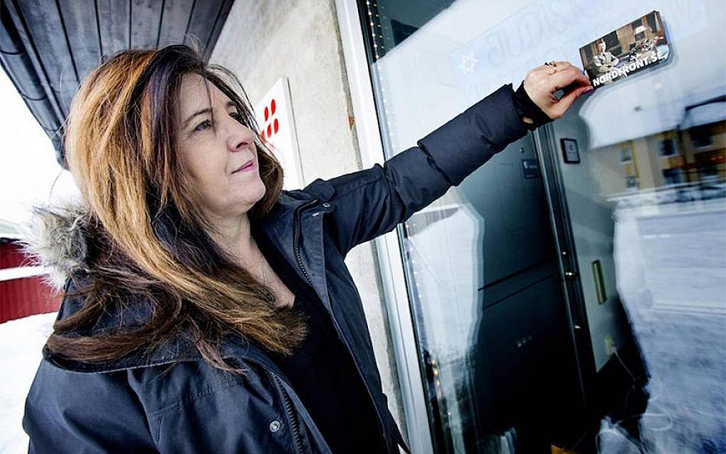 Carinne Sjoberg peeling off a sticker that neo-Nazis left on the door of what used to be the Jewish community center of Umea, Sweden. (Photo Courtesy of Sjoberg/via JTA)