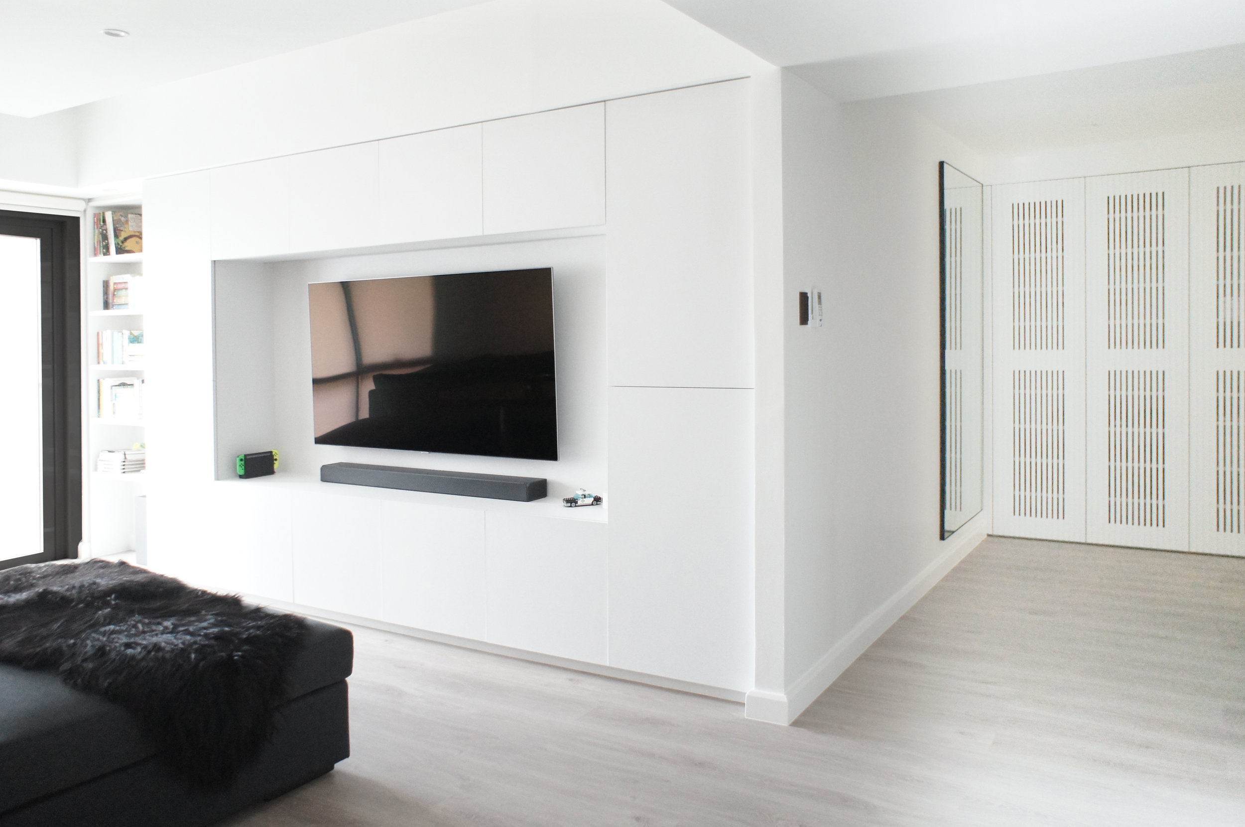 A fully built out media wall with floor to ceiling storage and precise measurements inside to house all media equipment. A narrow area is allocated to frequently read books.