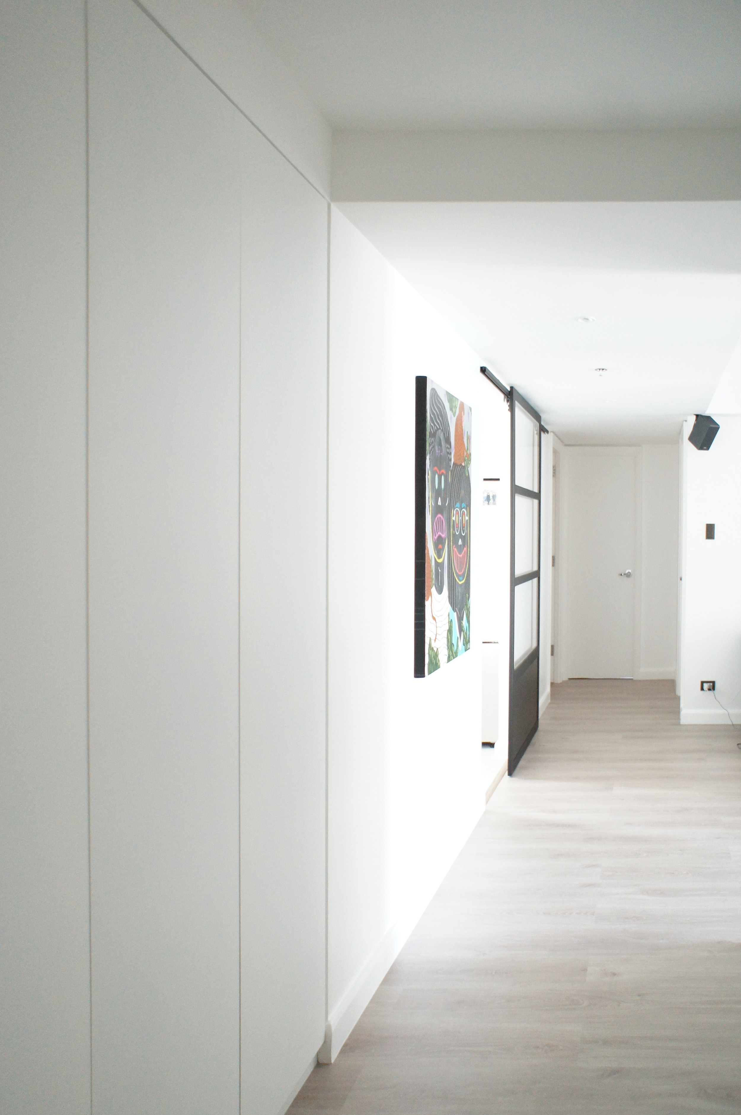 The apartment's palette of light wood, dark linen upholstery and matte white lacquer repeats itself in the entire home. The all white space provides a ready backdrop for the quickly growing art collection.  Additional floor to ceiling storage was carved out in the hallway. The built ins also serve the purpose of evening out the long wall. The kitchen is separated from the main living space by a metal framed glass sliding door. The kitchen cabinets utilize the same detail as the cabinets in the main living space, creating a continuous look throughout.