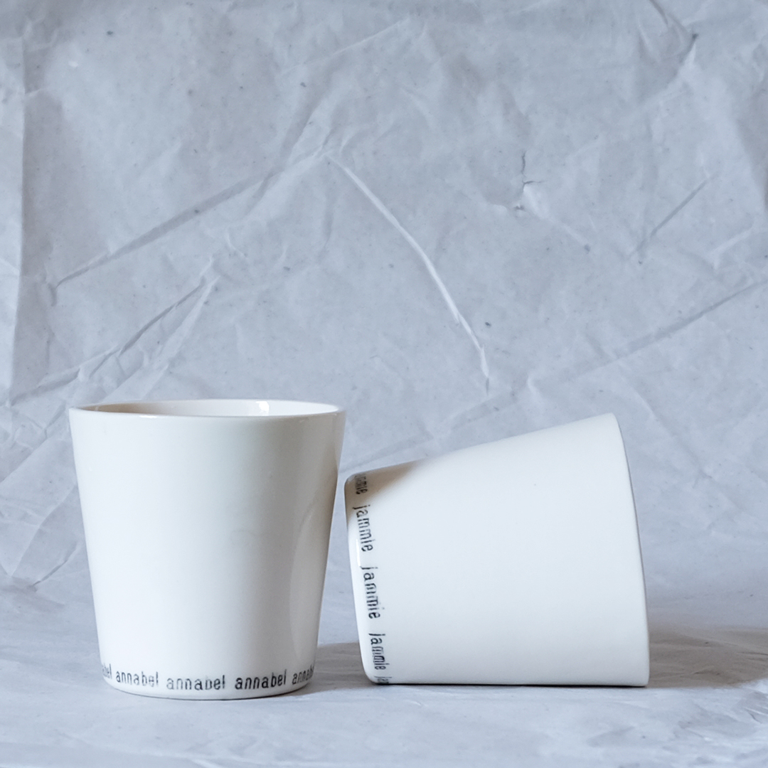 A pair of personalised porcelain beakers to be given as a wedding gift.