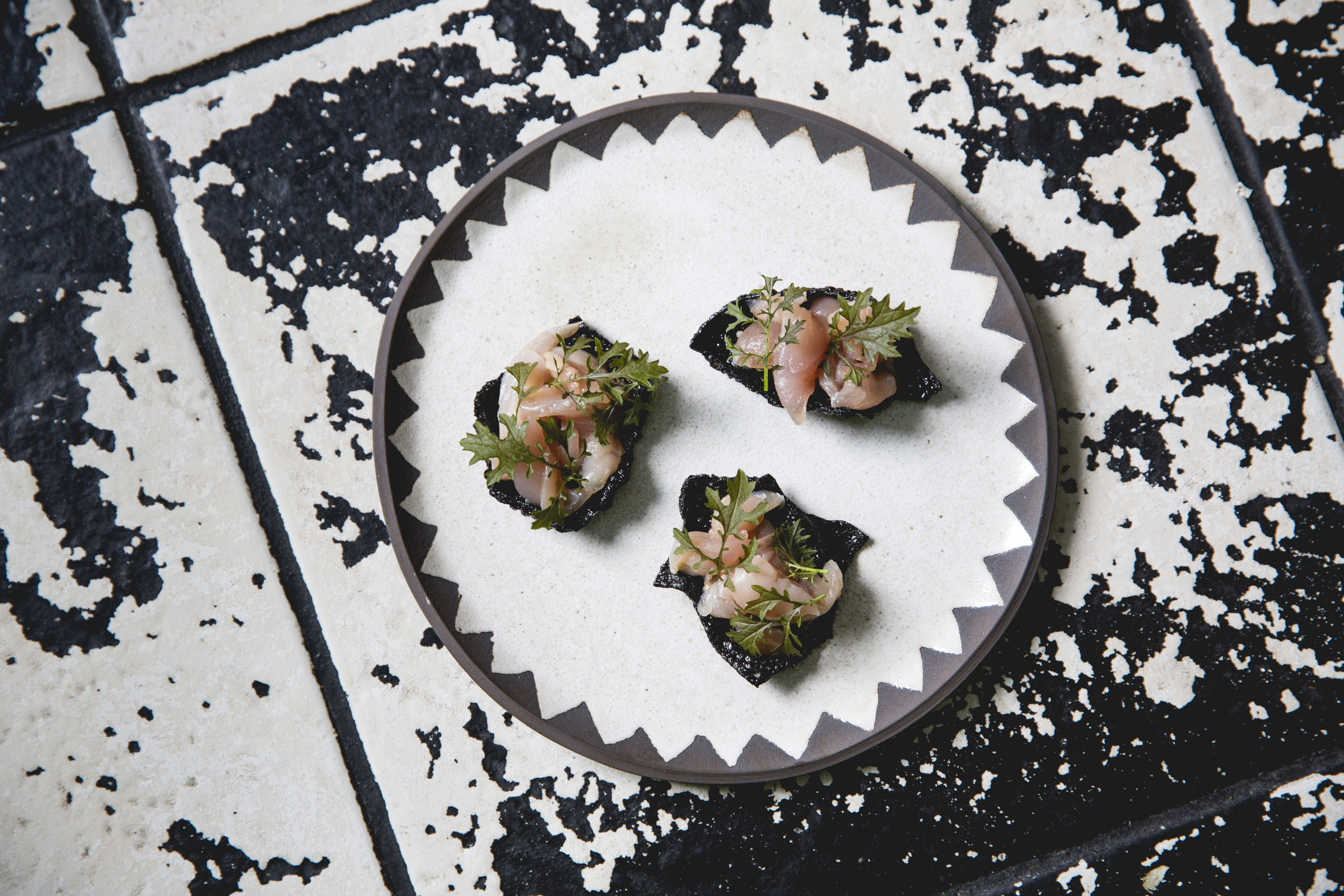 Black Boom plate. Mackerel dressed in tosazu on a squid ink cracker with mustard frill.