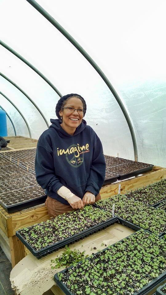 Lorrie in the Rise + Root's greenhouse with well-watered seedlings!