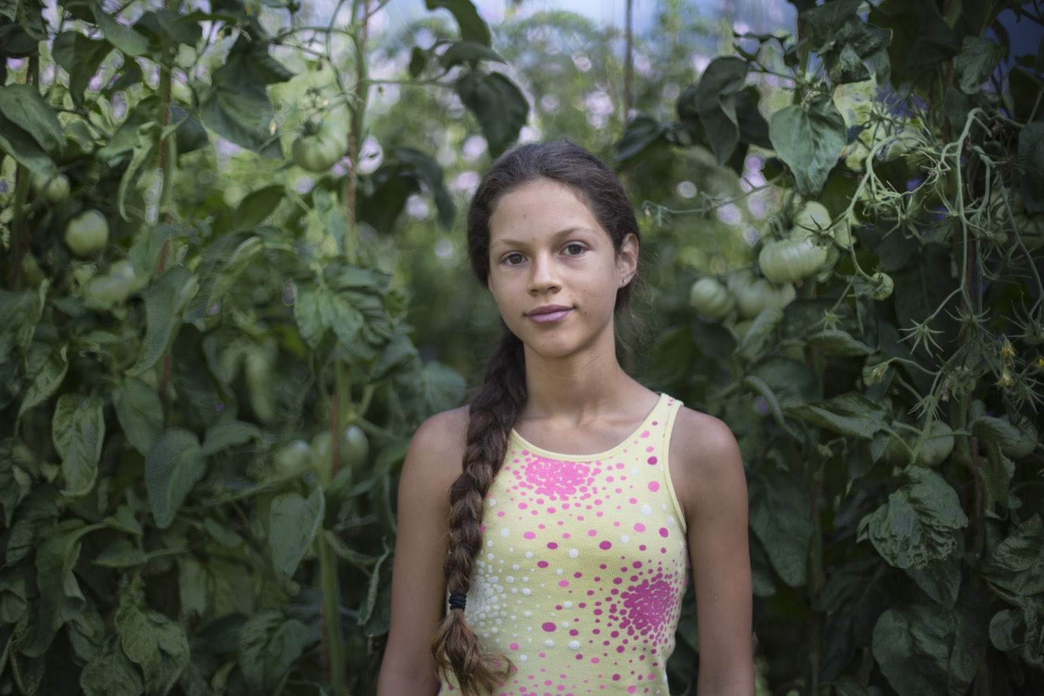 Farmers daughter, Nyanza, in the greenhouse after harvesting tomatoes. (British Columbia)