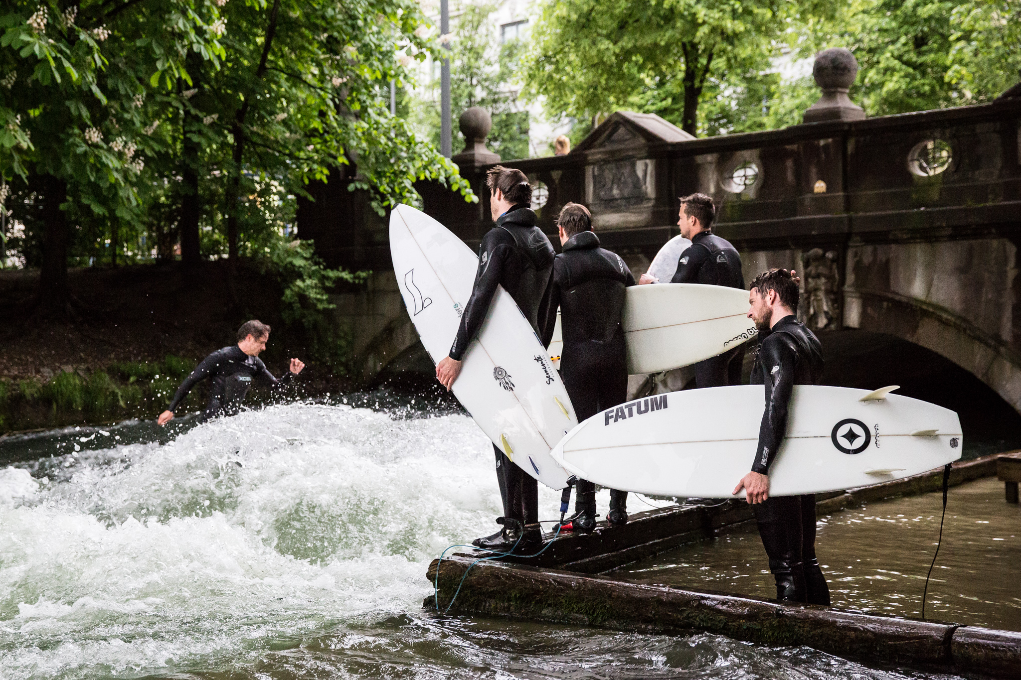 surfers surfing on eisbach river munich