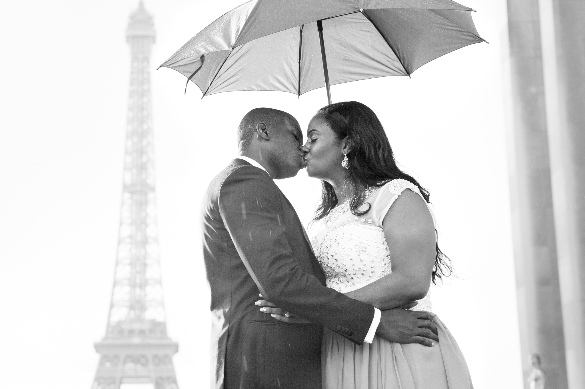 couple kissing by eiffel tower to celebrate their engagement