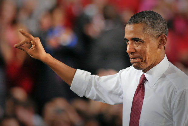 "President Barack Obama gives the Wolfpack hand sign as a salute to the ""Think and Do"" mentality of NC State during his visit."