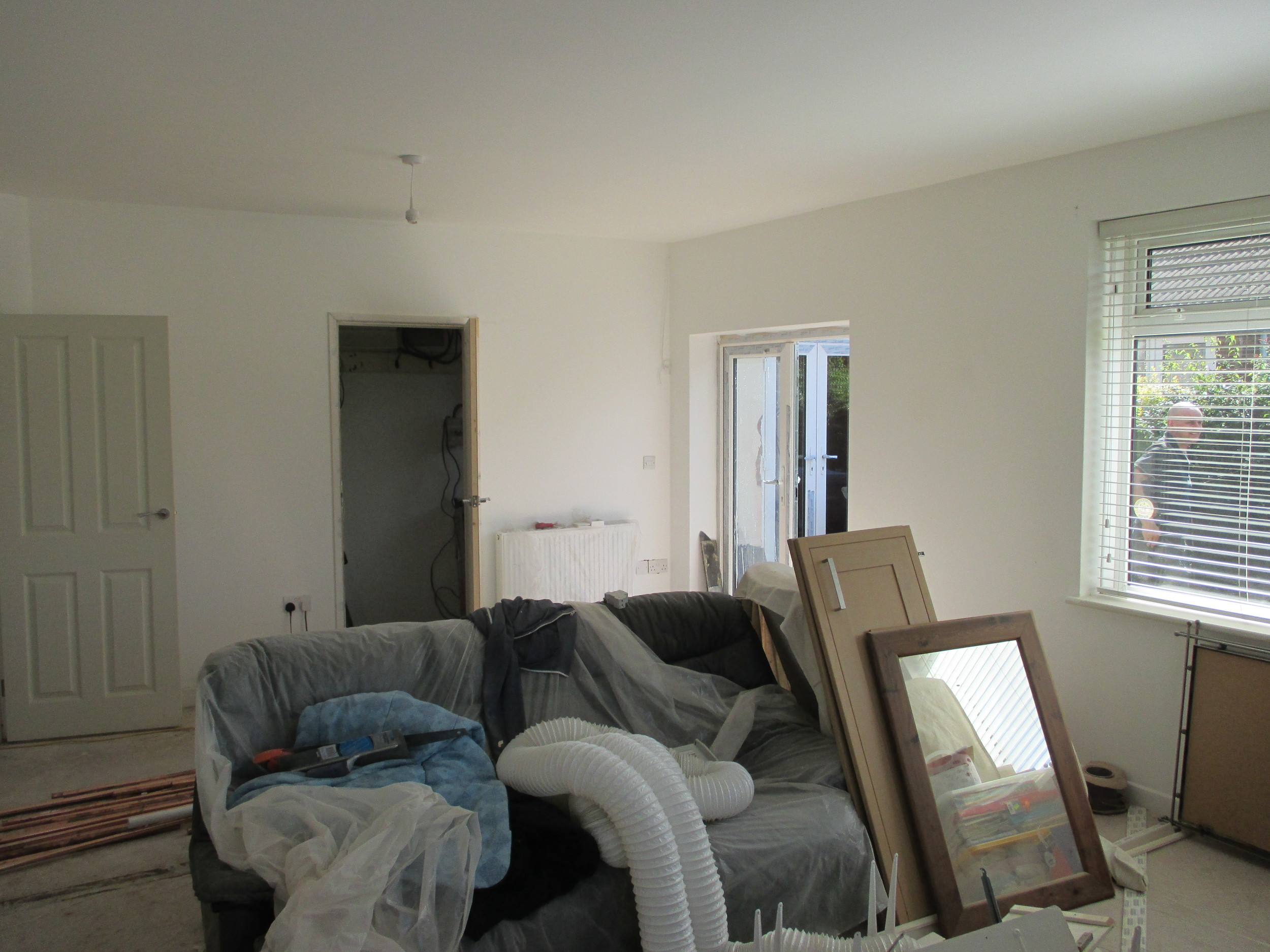 Conversion in Progress - Living room now incorporating the old hall space with old front door area converted into patio doors into courtyard garden.