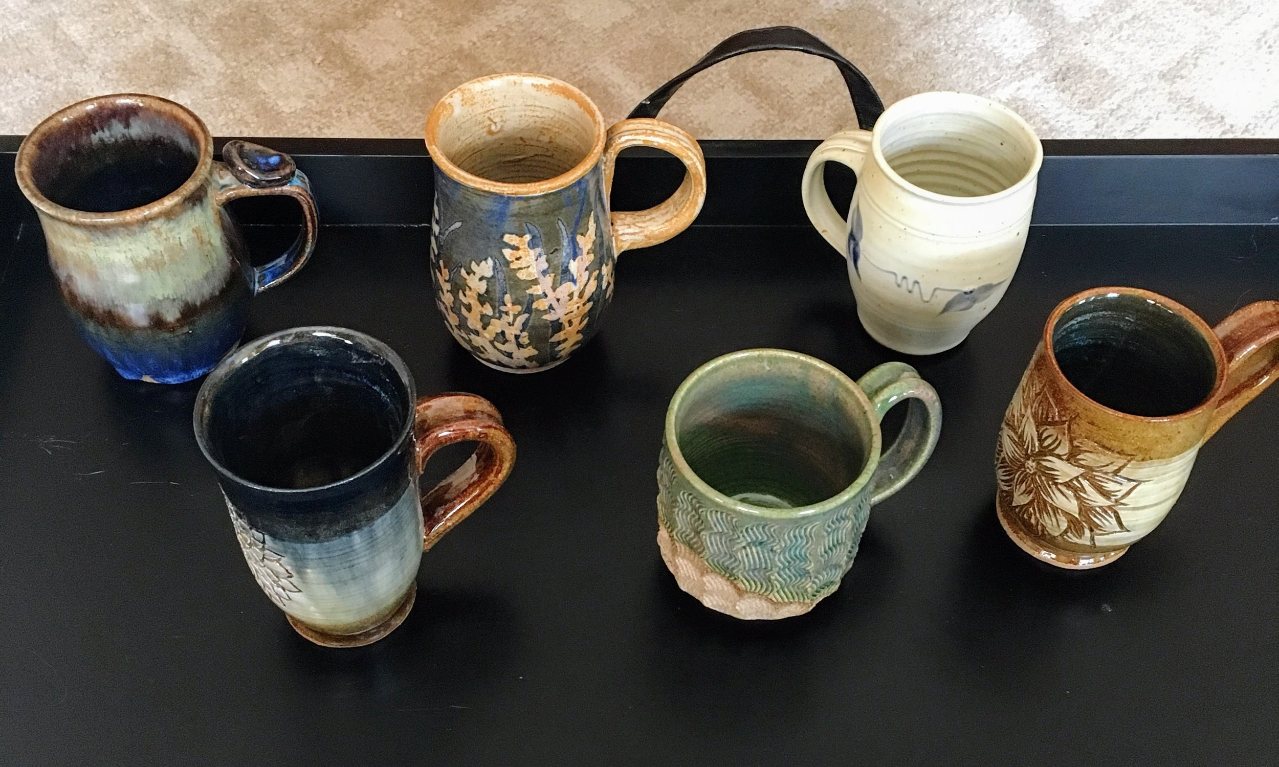 Top Row: First two are collaboration mugs made by myself,  Kaila Braley , and  Britt Tekla Drews  and third is from  Barking Spider Pottery Studio   Bottom Row: Mug made by myself, middle mug was made by W ater Dragon Pottery Studio from Halifax, Nova Scotia , and the third is one of mine.