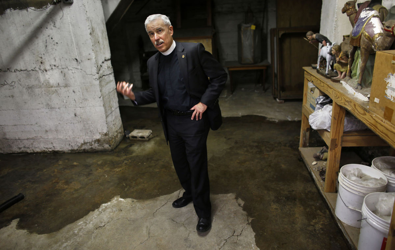 The Rev. Win Lewis shows how even on a sunny day, March 21, 2017, water can accumulate in the basement of Christ & St. Luke's Episcopal Church in Norfolk, which stands just across the street from the flood-prone Hague.