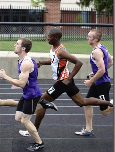 Mark, center, competed in high school and college track. He coaches track now.
