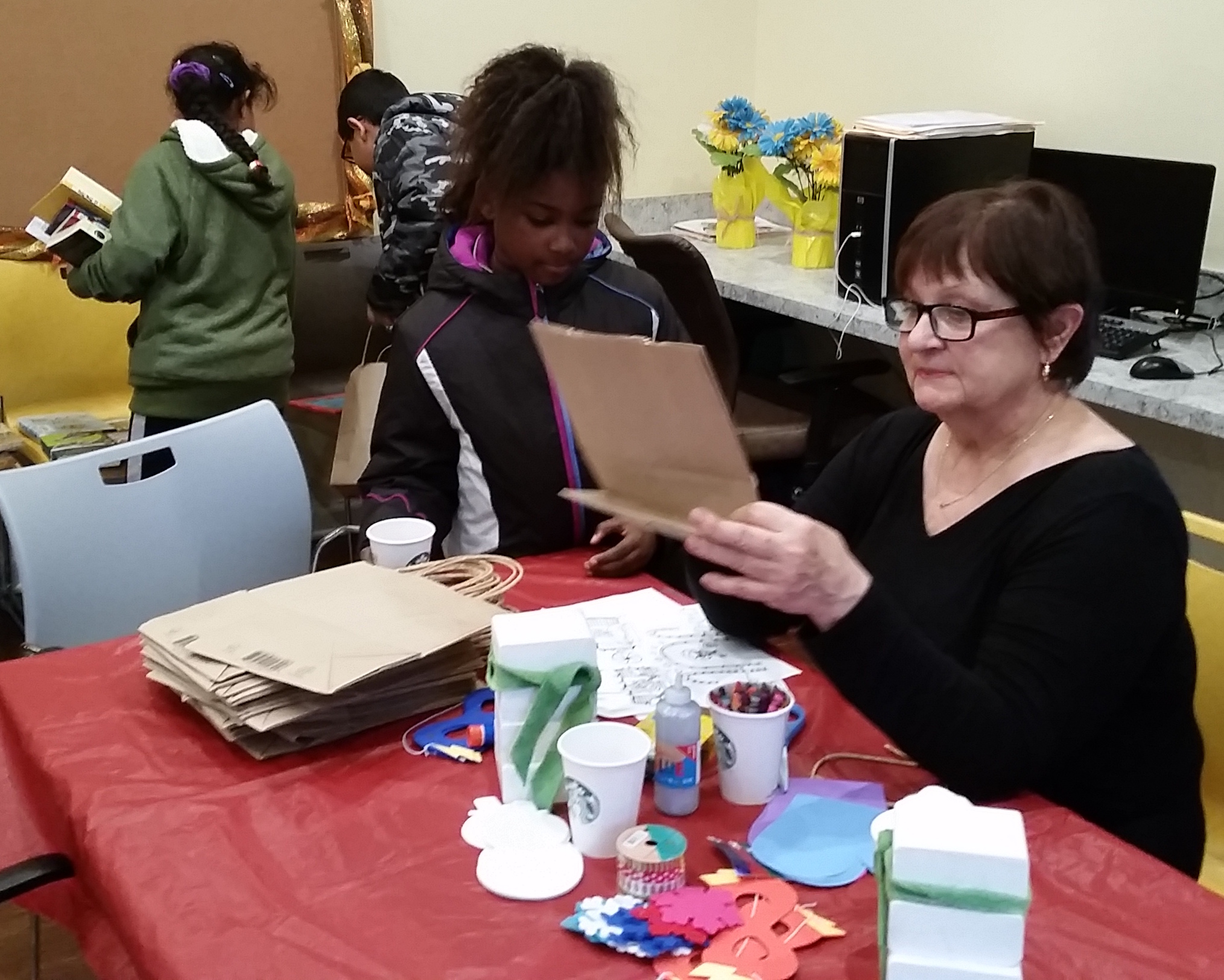 Deb Coffelt helps young Trabue Crossing resident make a ginger bread house