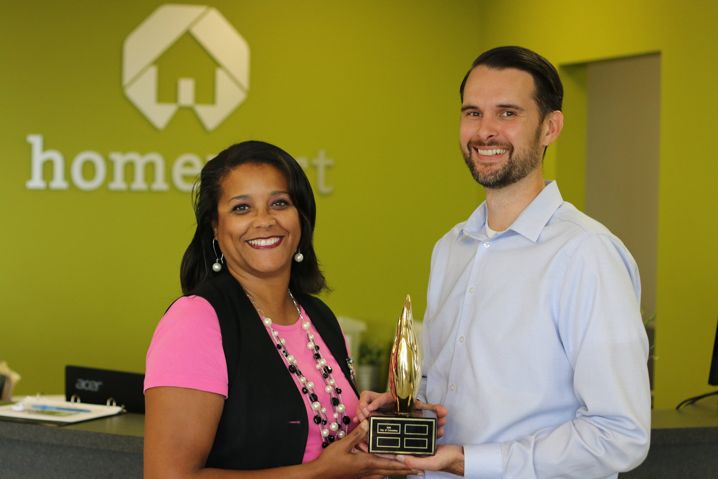 Laverne Price and Alex Romstedt hold trophy Homeport has held since Columbus was awarded host city for the 2016 NeighborWorks America Community Leadership Institute.