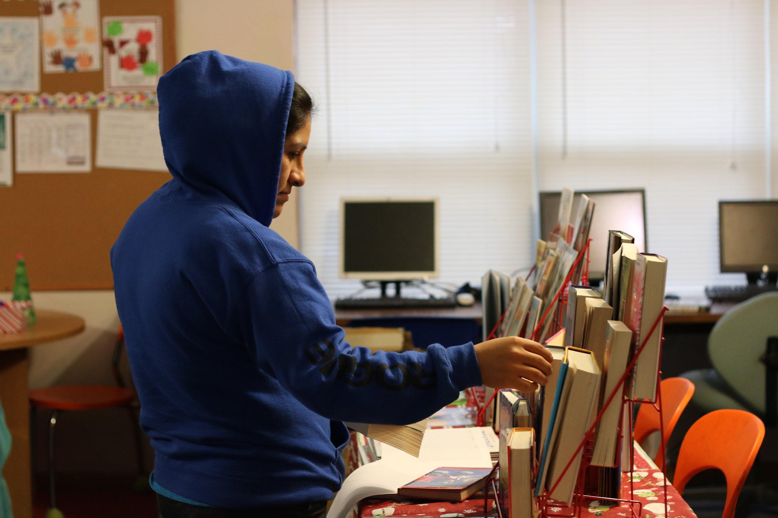Emerald Glen's Lourdes Cruz checks out books for her three girls