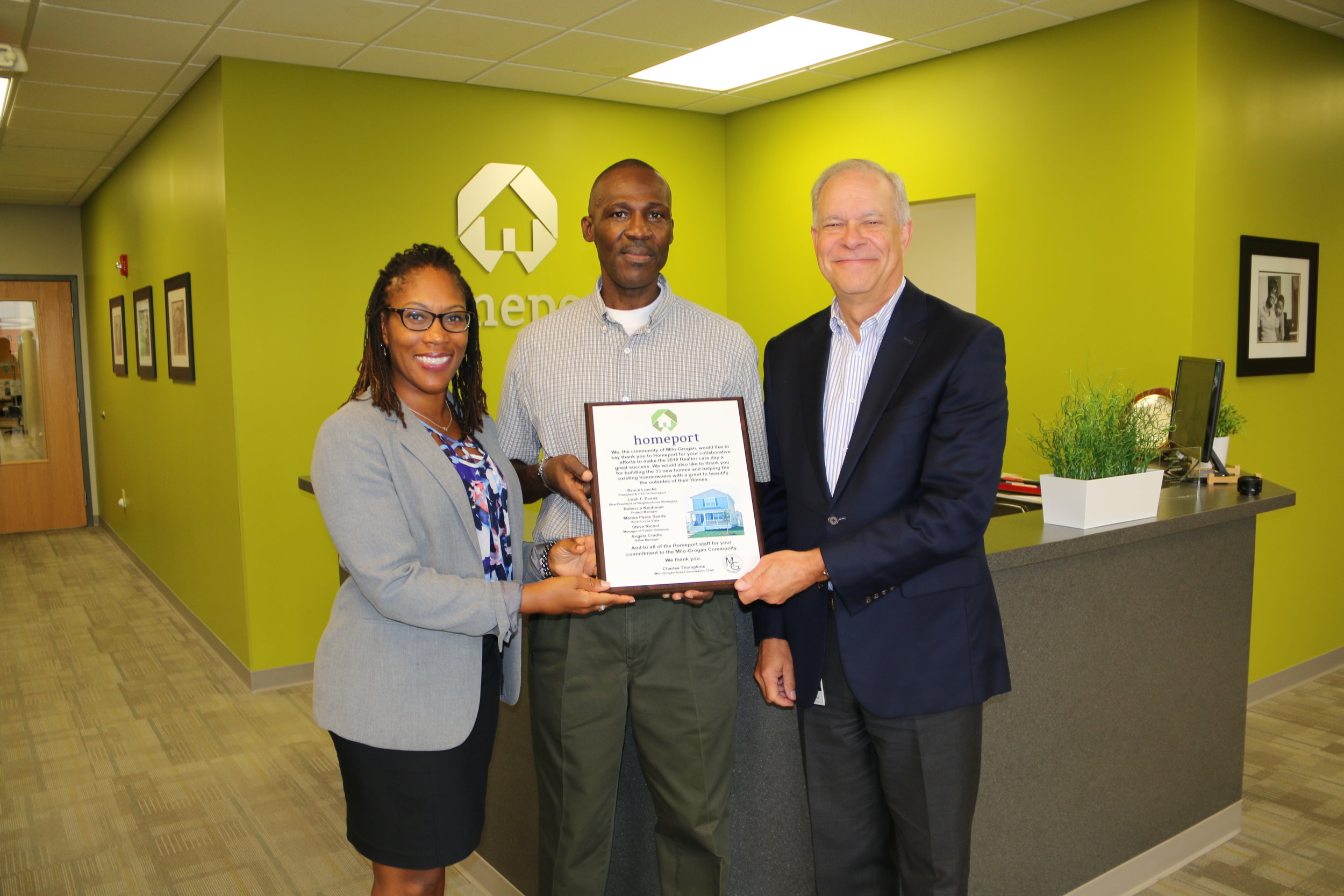 Homeport Vice President of Neighborhood Strategy Leah Evans, left, and Homeport President & CEO Bruce Luecke, right, accepted a plaque of thanks from Milo-Grogan Area Commission Chair Charles Thompkins .