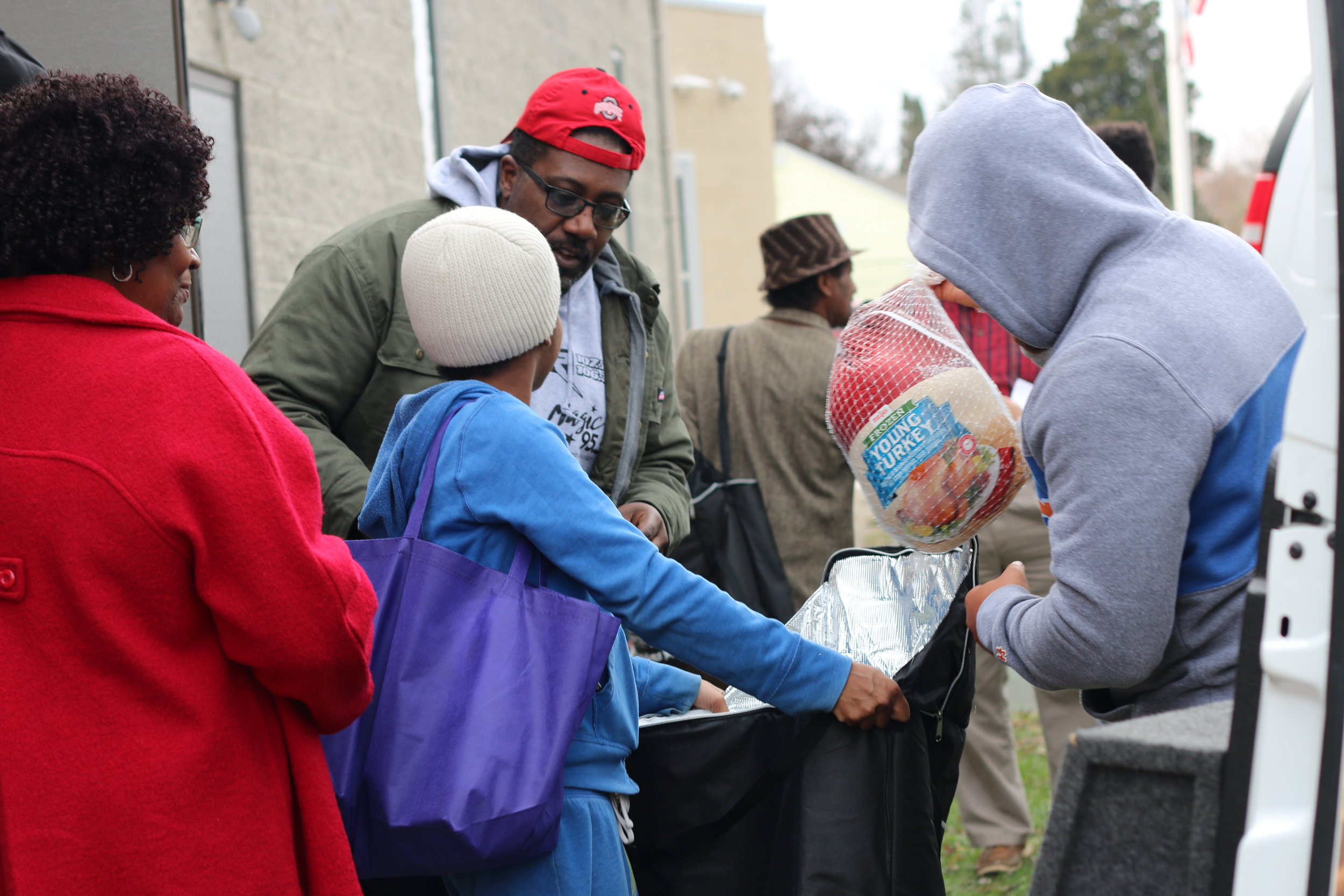 """Joy 107.1 on-air personality """"City"""" greets resident receiving a Thanksgiving turkey from the station."""