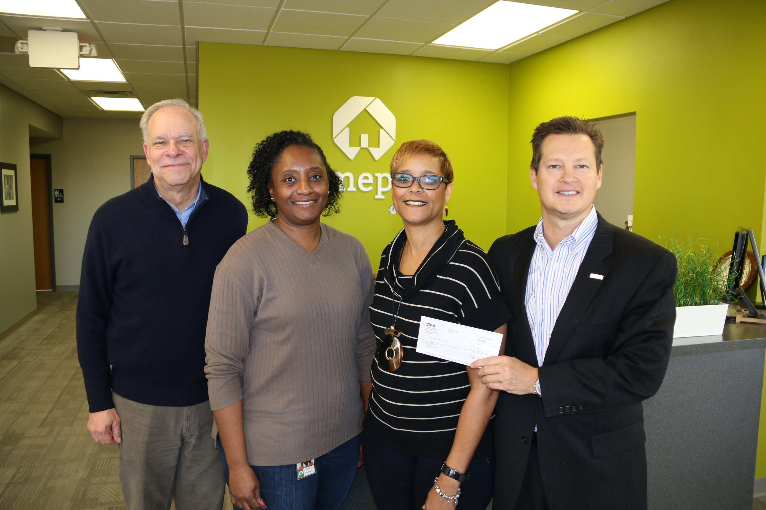 Homeport's Bruce Luecke, Netta Whitman and Laverne Price accept U.S. Bank gift from Stephen Bennett, right.