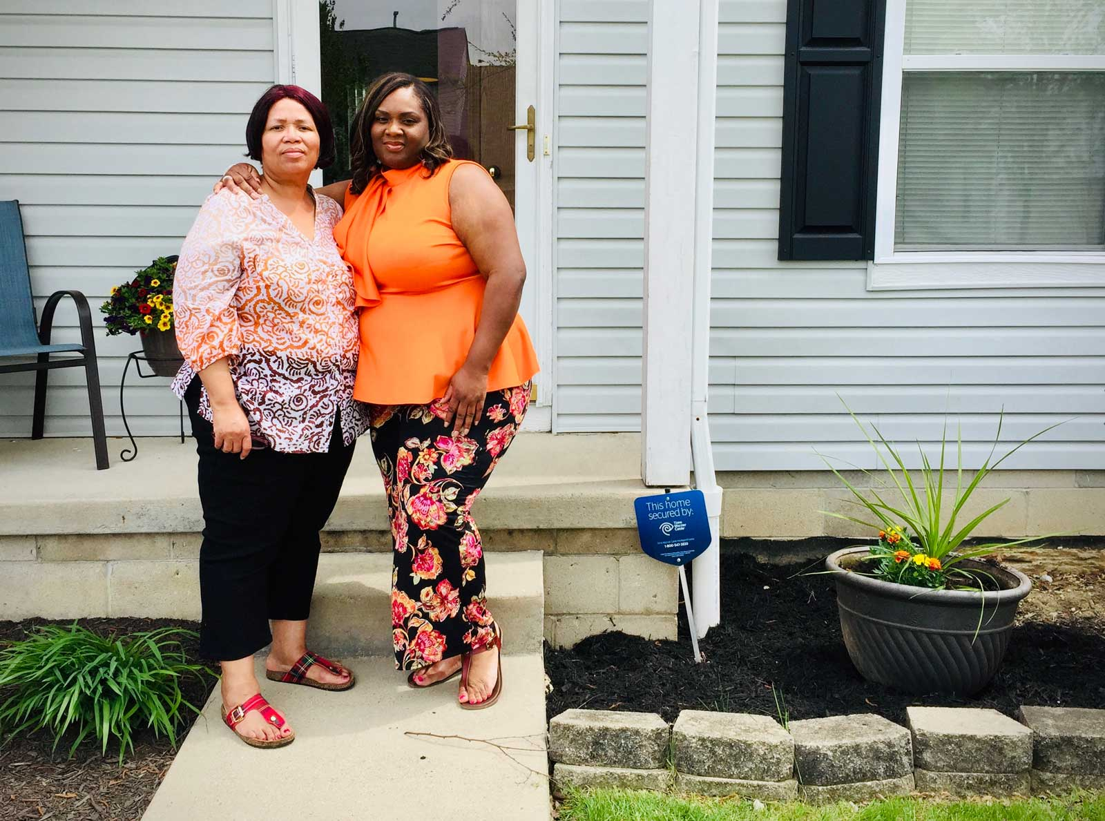 Essie with her daughter Kanica, in front of Kanica's home.
