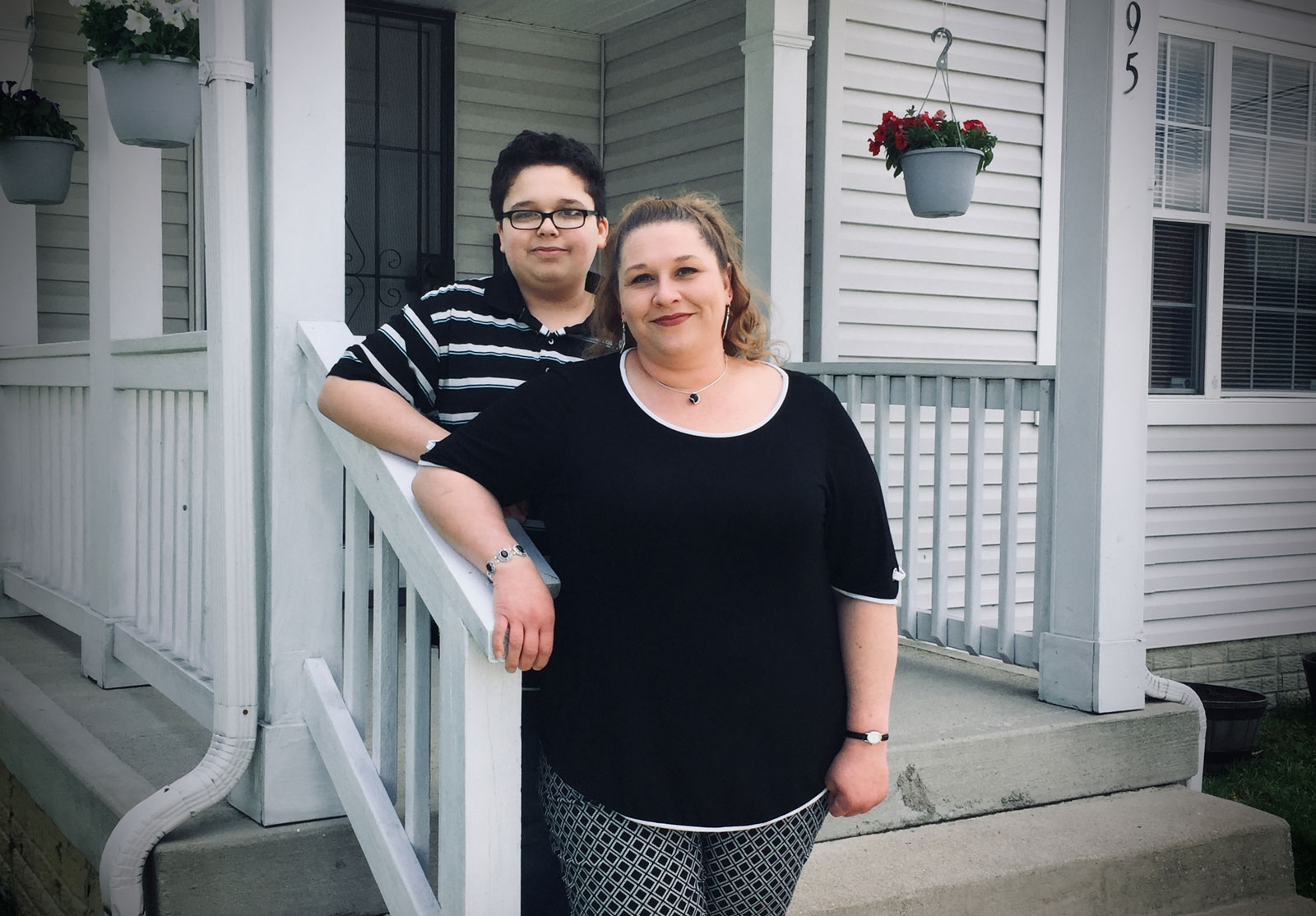 Maggie with her son Bryan in front of their home.