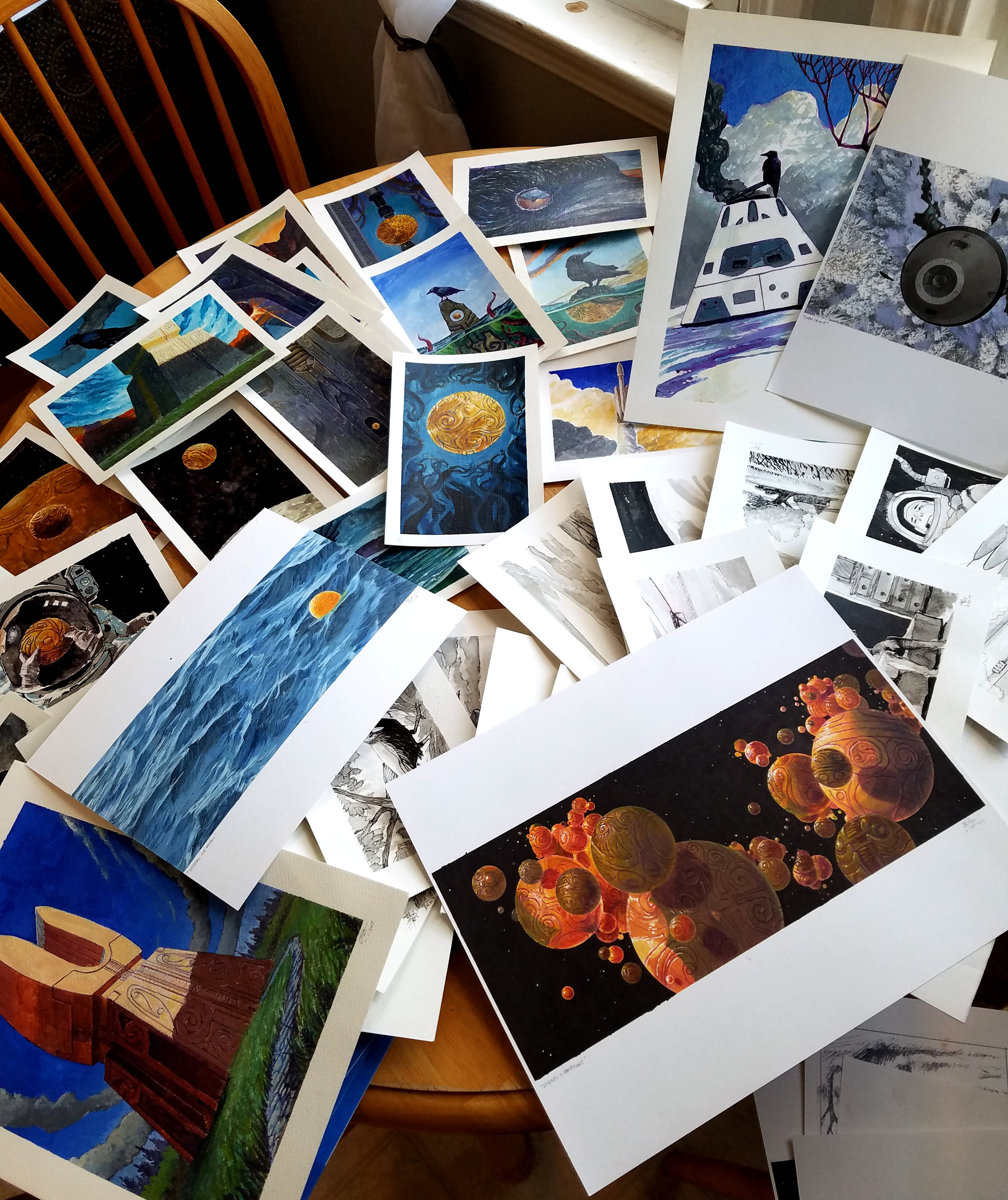 My kitchen table full of the illustrations completed so far. Note:many are buried in layers there...