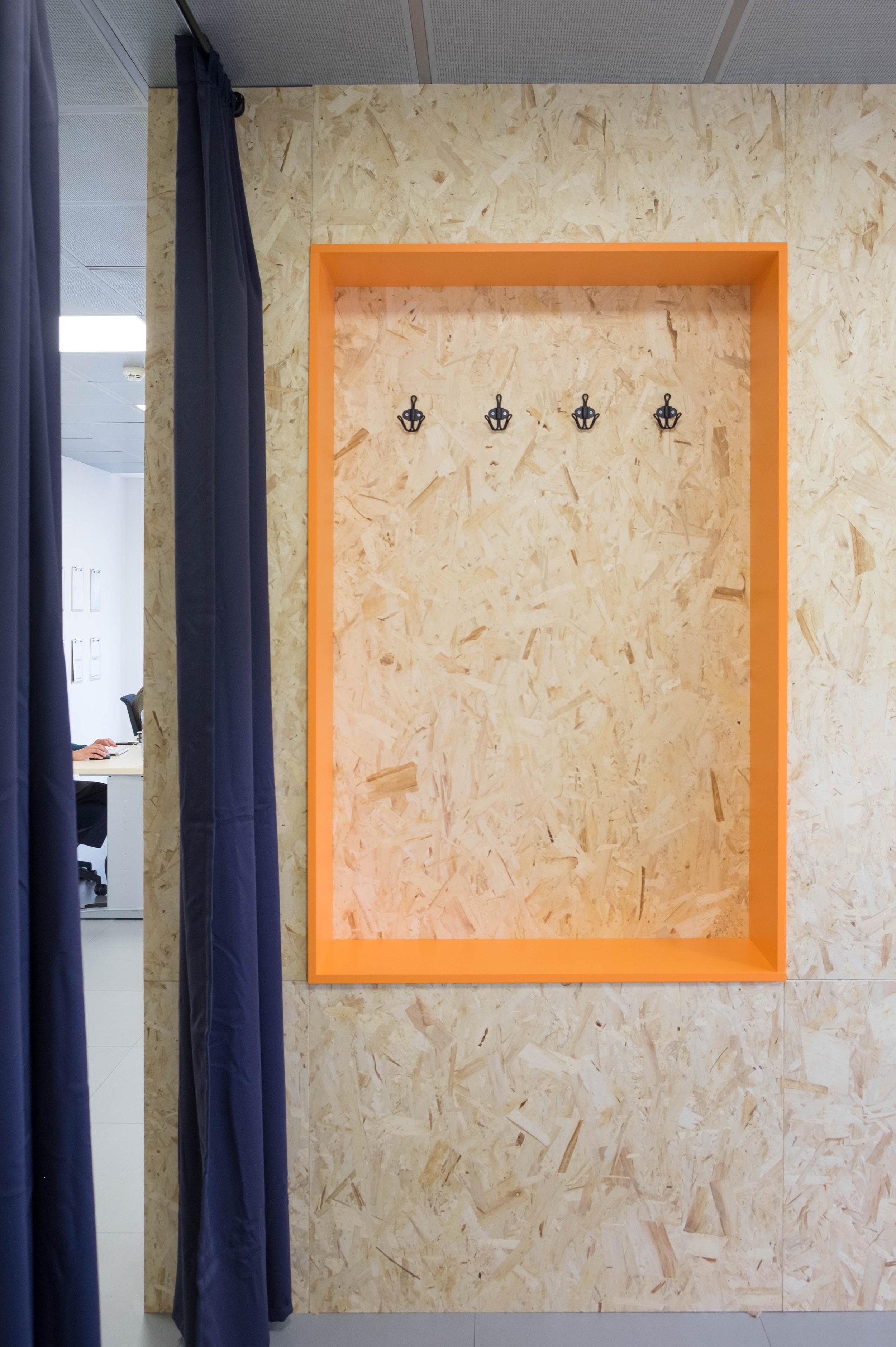 Detalle del espacio para dejar bolsas i chaquetas dentro de la sala de reuniones.