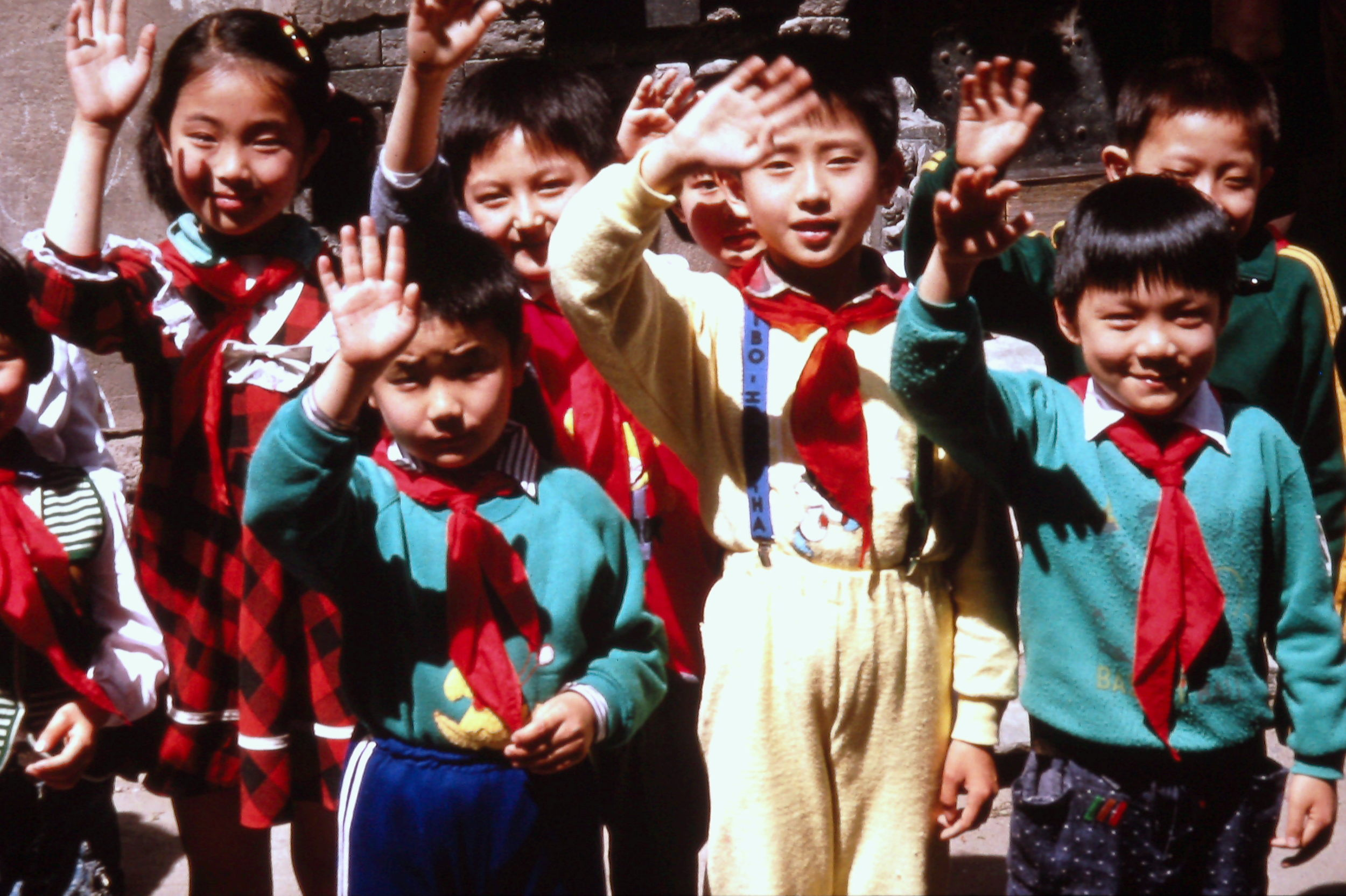 Children on the street wave to the Trans-Antarctica bus as it travels through Beijing, China, May 1990. Photo: Cathy de Moll