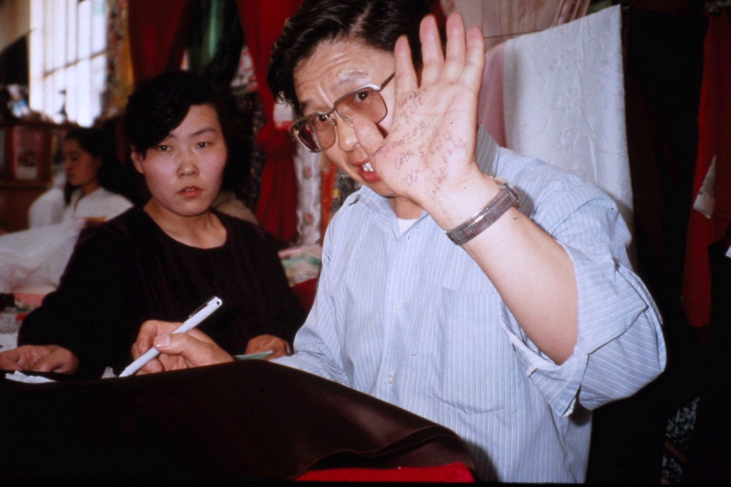 Li Zhangsheng tracks our silk purchases on his hand. Lanzhou, China, May 1990. Photo: Cathy de Moll
