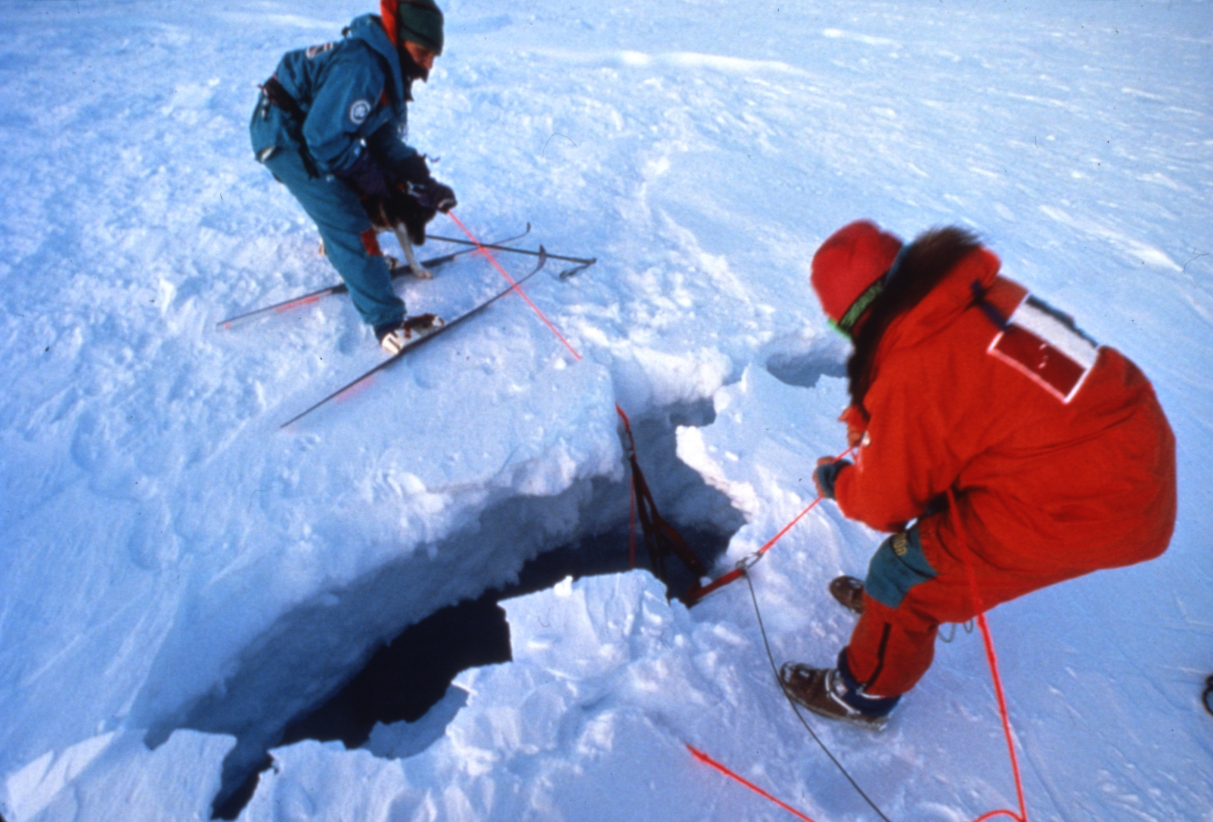 Geoff Somers (left) and Jean-Louis Etienne (right) work to extract a dog from a crevasse without falling in themselves. Photo © Will Steger