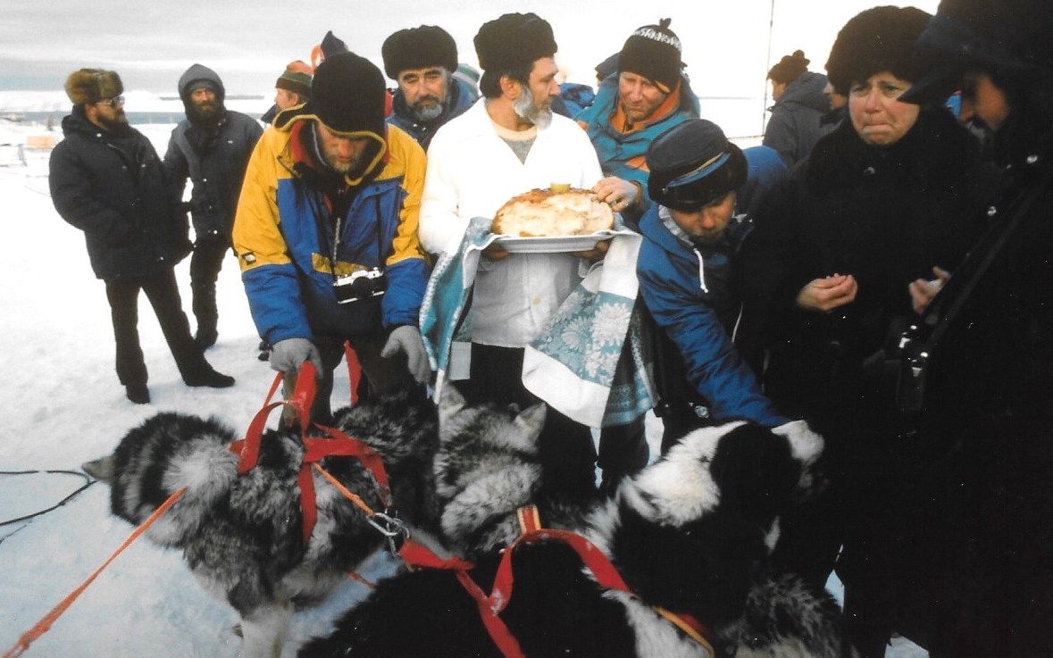 Traditional Russian salted bread dipped in vodka greets the Trans-Antarctica team at the finish line. JP (in yellow) takes over the dogs. ©Trans-Antarctica, photo by Per Breiehagen