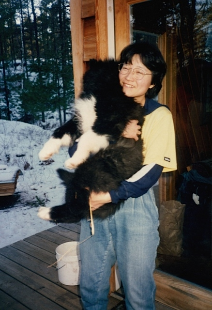 Yasue cuddles a puppy at the Homestead. Photographer unknown