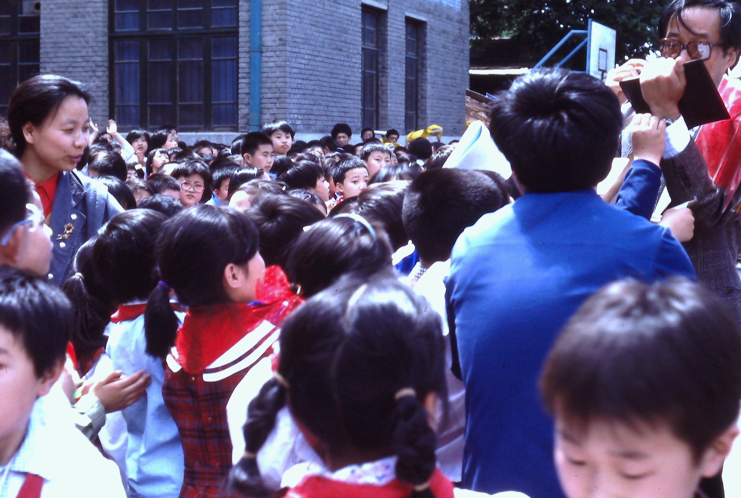 Expedition team member Qin Dahe signs autographs for a sea of Beijing children at the successful completion of the nearly 4,000-mile 1990 International Trans-Antarctica Expedition.