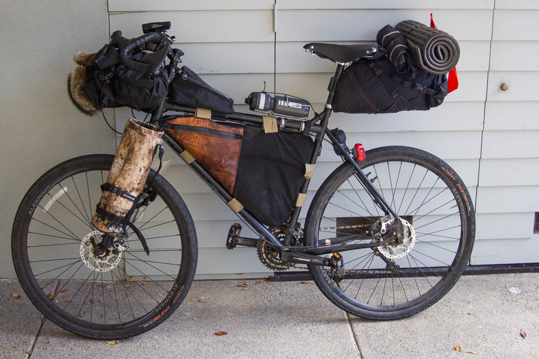 The tripod and platypus 2-liter water bladder sit on either side of my fork in cages with straps.