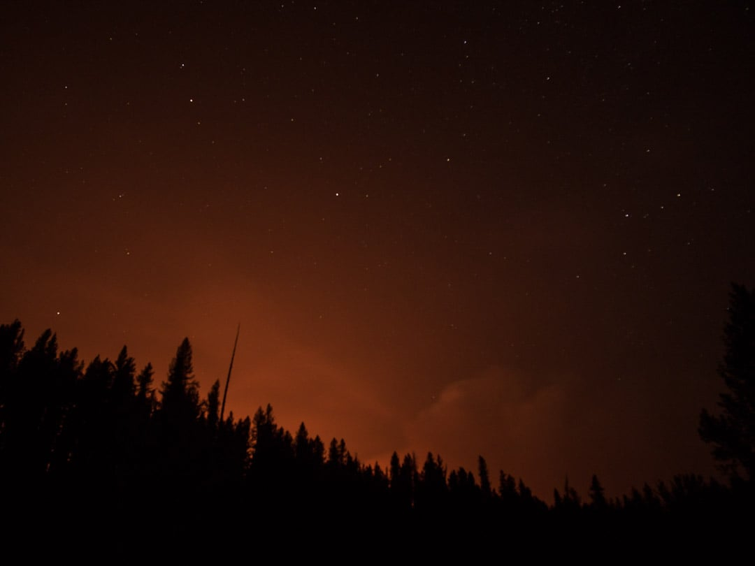 The Bear Creek fire glows over the ridge from our final camp. There was no choice but to evacuate - Photo: Colin Arisman