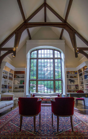 The cathedral room, so named because of its buttressed ceiling and arched window, is one of the house's formal areas. A blue, red, and cream rug sets the tone.