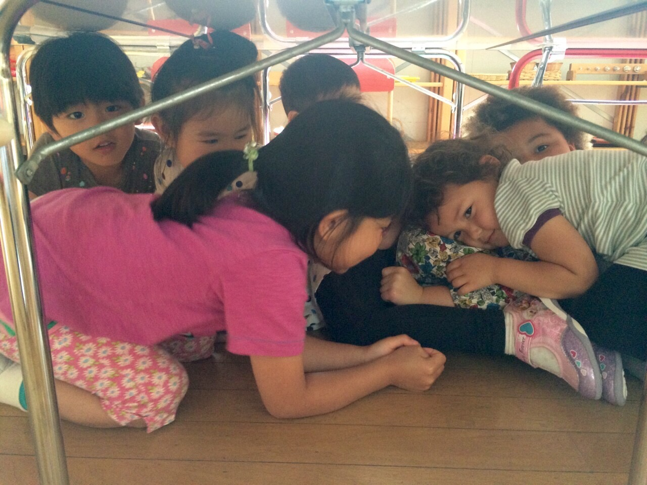 Children practicing going under the table.